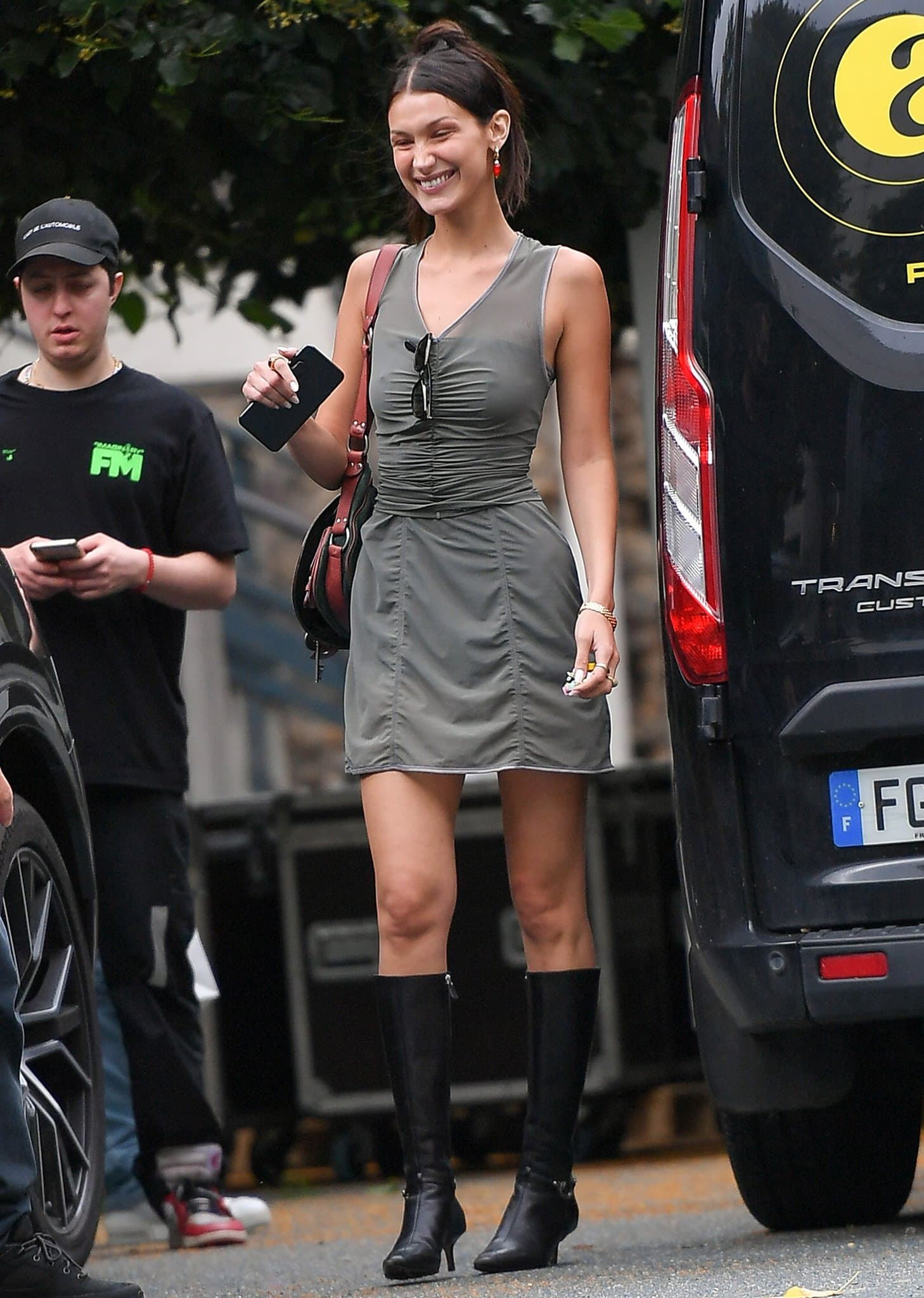 Bella Hadid leaving Off-White runway show during Paris Fashion Week in olive green mini dress and boots on July 4, 2021