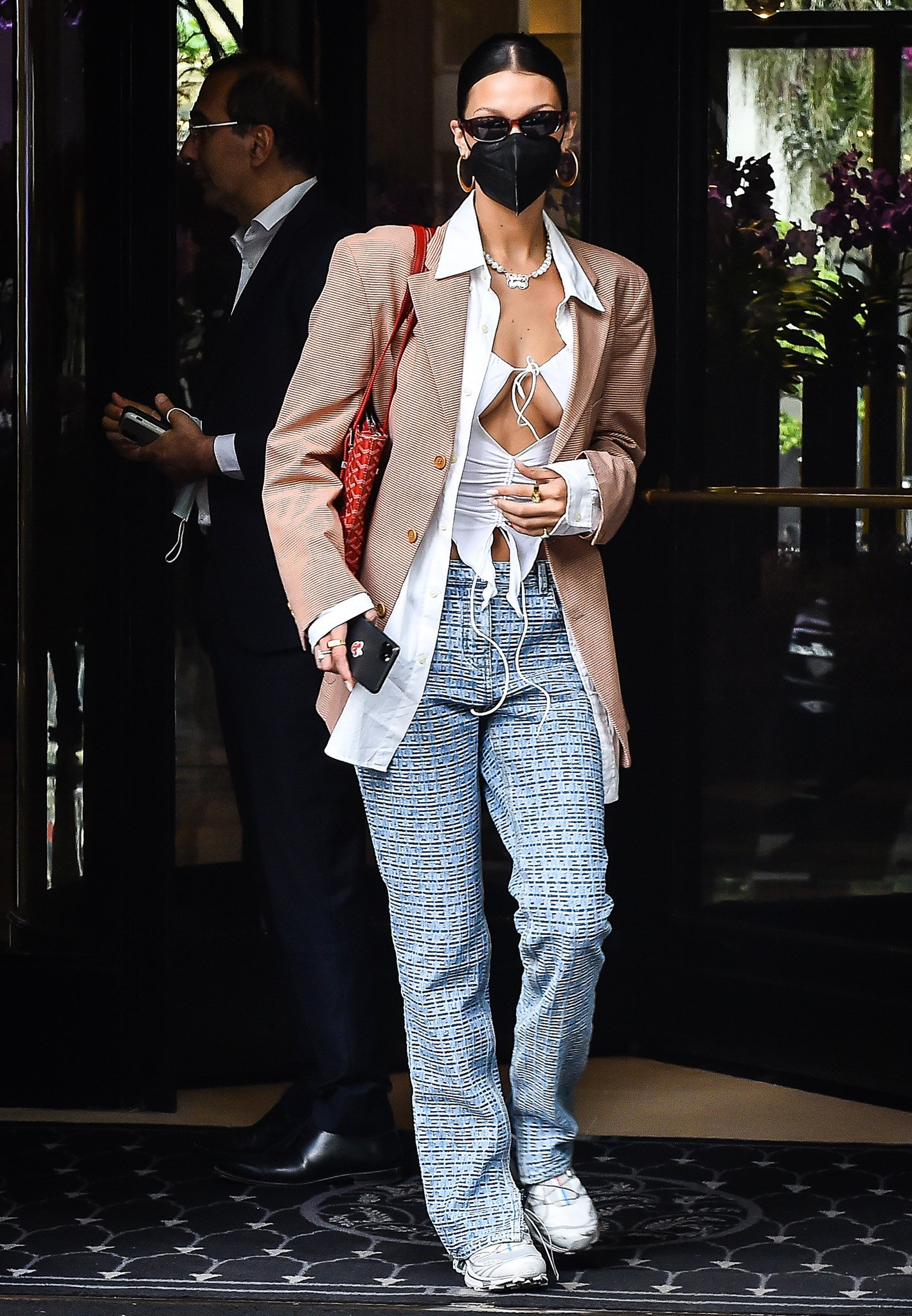 Bella Hadid flashes her abs and cleavage in an I.Am.Gia Svana white top with white shirt, red checkered blazer, and Givenchy pants