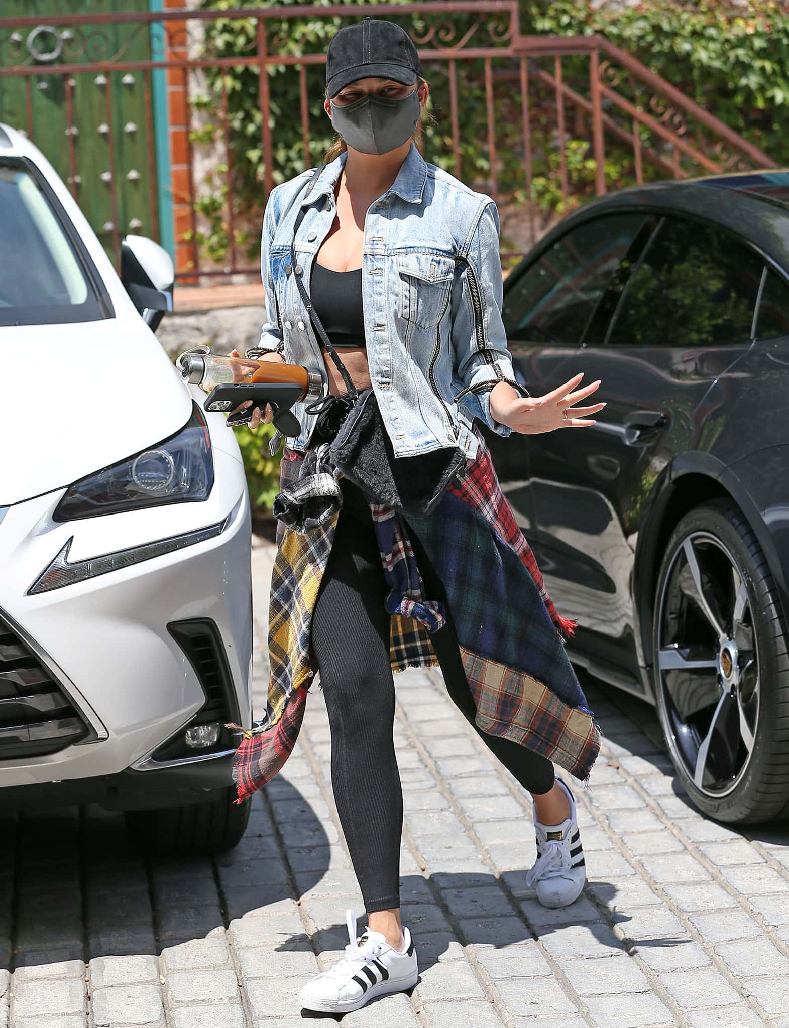 Chrissy Teigen layers a 3.1 Phillip Lim denim jacket and a plaid R13 shirt over her sports bra and leggings
