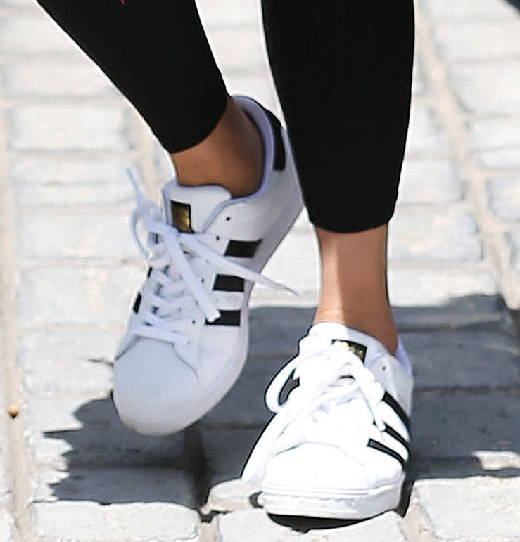 Chrissy Teigen pairs her effortlessly cool outfit with the classic Adidas Superstar sneakers