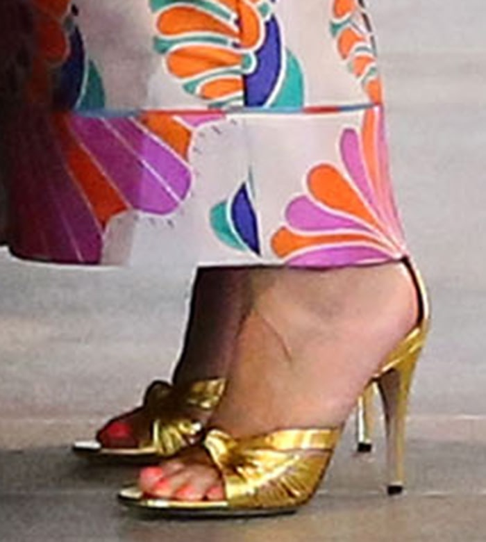 Chrissy Teigen completes her relaxed yet glamorous ensemble with gold Gucci Crawford knotted sandals