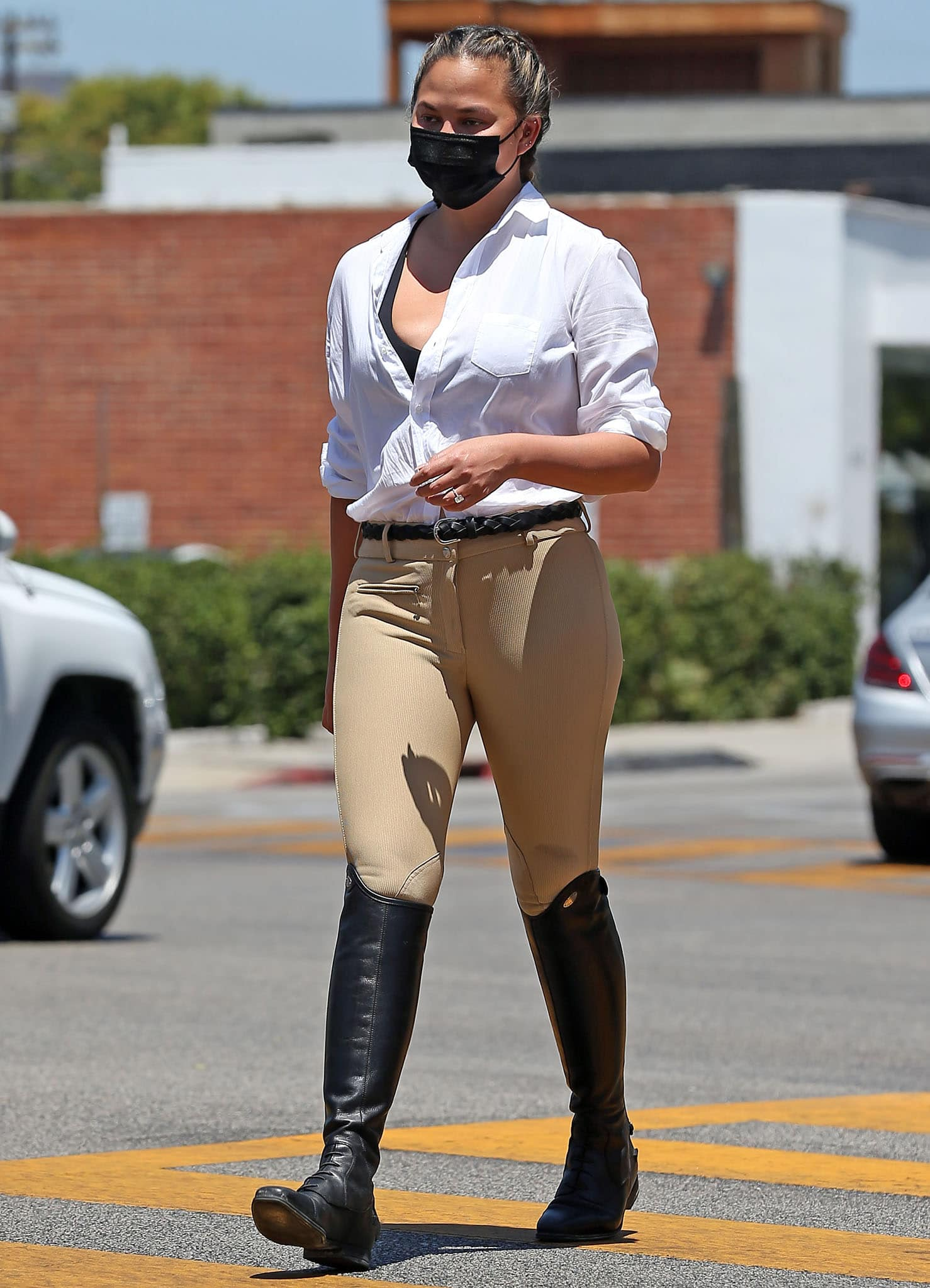 Chrissy Teigen opts for an equestrian-inspired outfit with Frank & Eileen white shirt, Tuffrider pants, and Isabel Marant belt