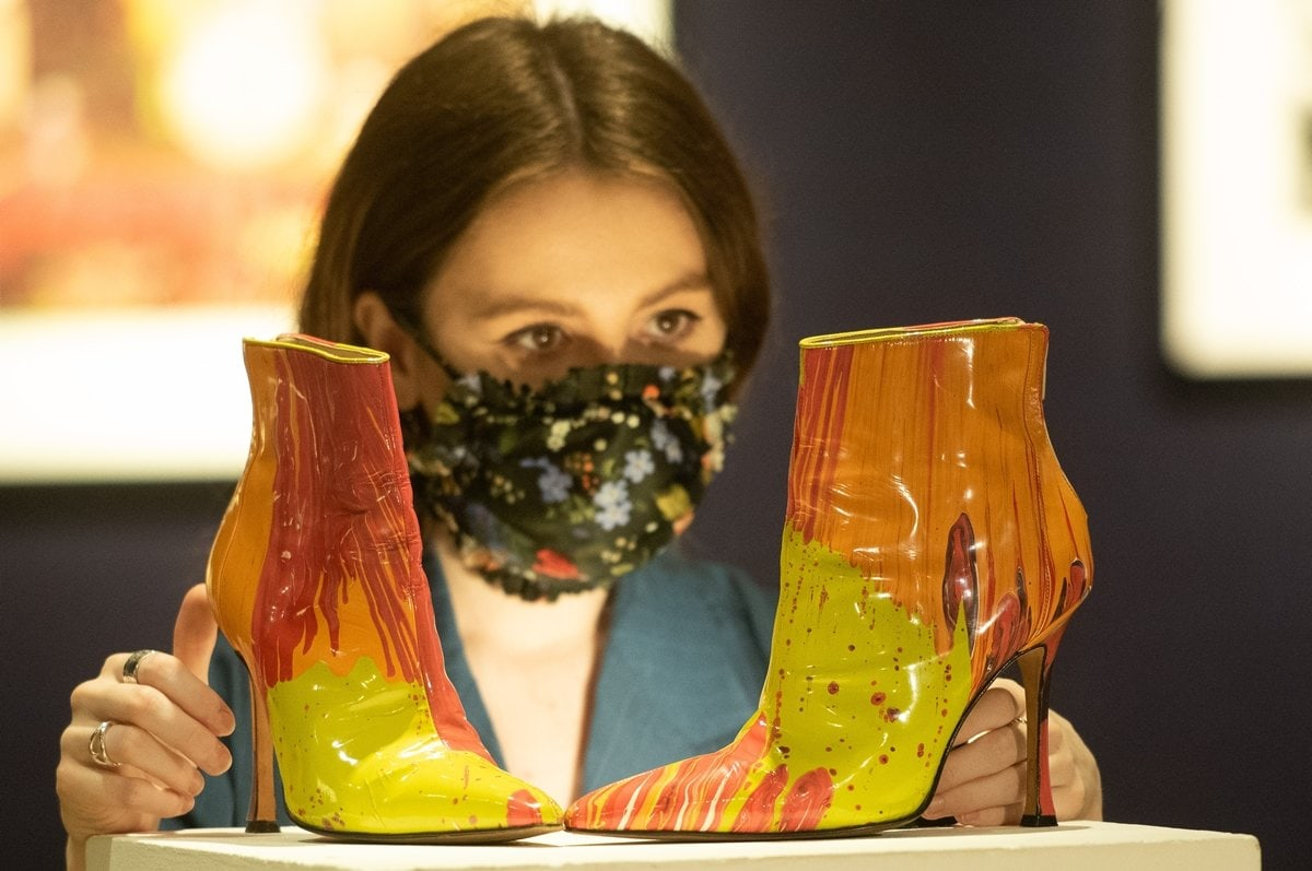 A gallery staff member poses with Damien Hirst X Manolo Blahnik Spin boots