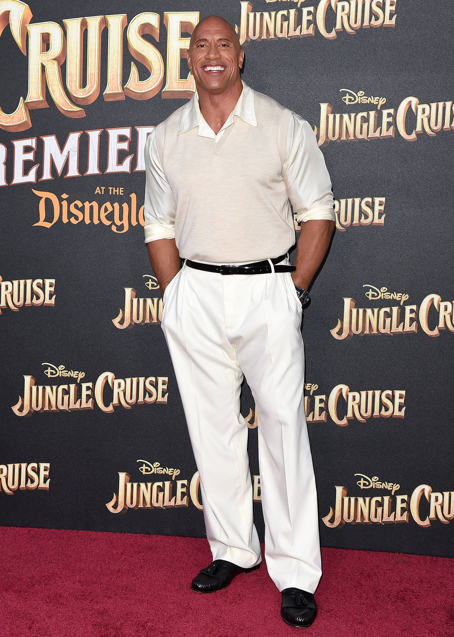Dwayne Johnson wears a sleeveless knit vest over a button-down shirt with white pants and black loafers