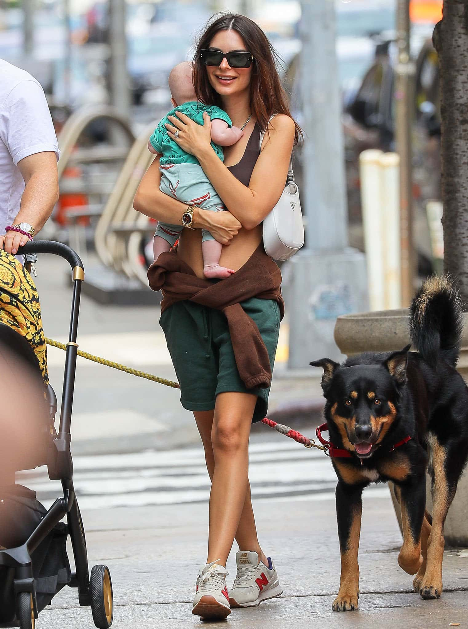Emily Ratajkowski cradles her son in her arms in a brown ENVT bra top and green long shorts