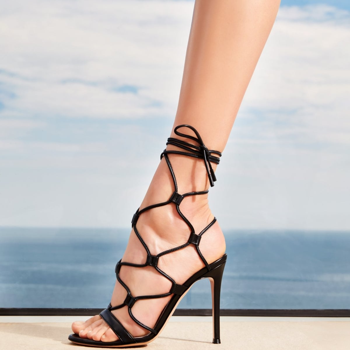 These black Gianvito Rossi Giza 105 leather sandals feature a round open toe, braided straps across the foot, ankle tie fastenings, and leather sole
