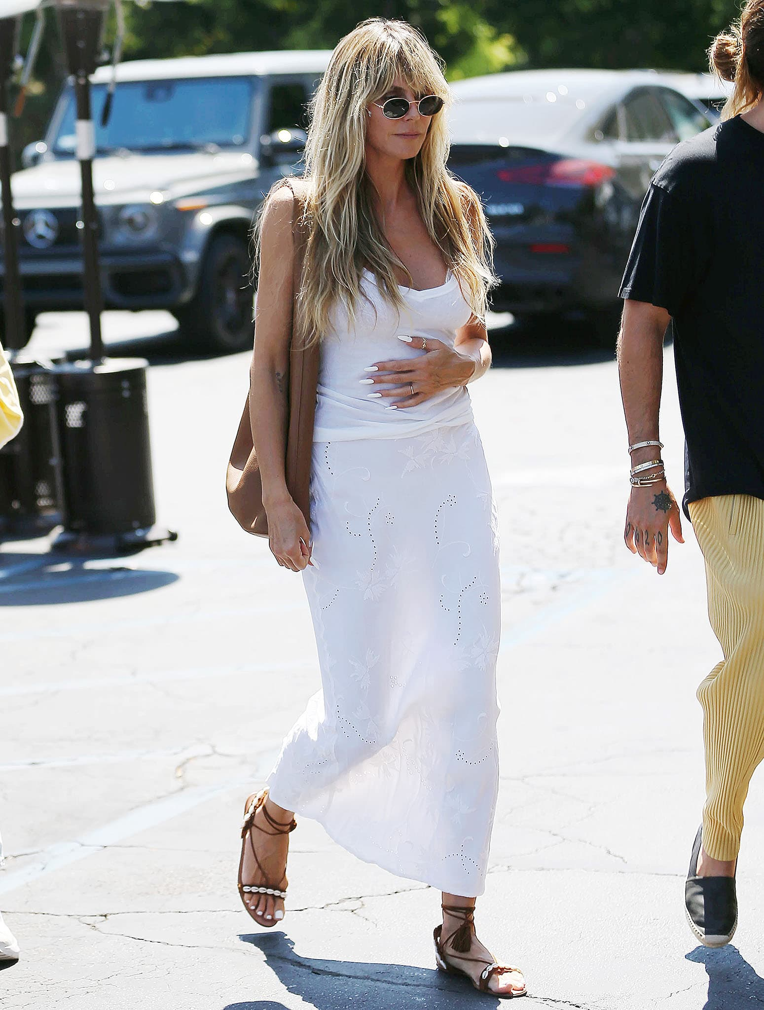 Heidi Klum showed a glimpse of her legs in a sheer white eyelet-detailed skirt and a white tank top