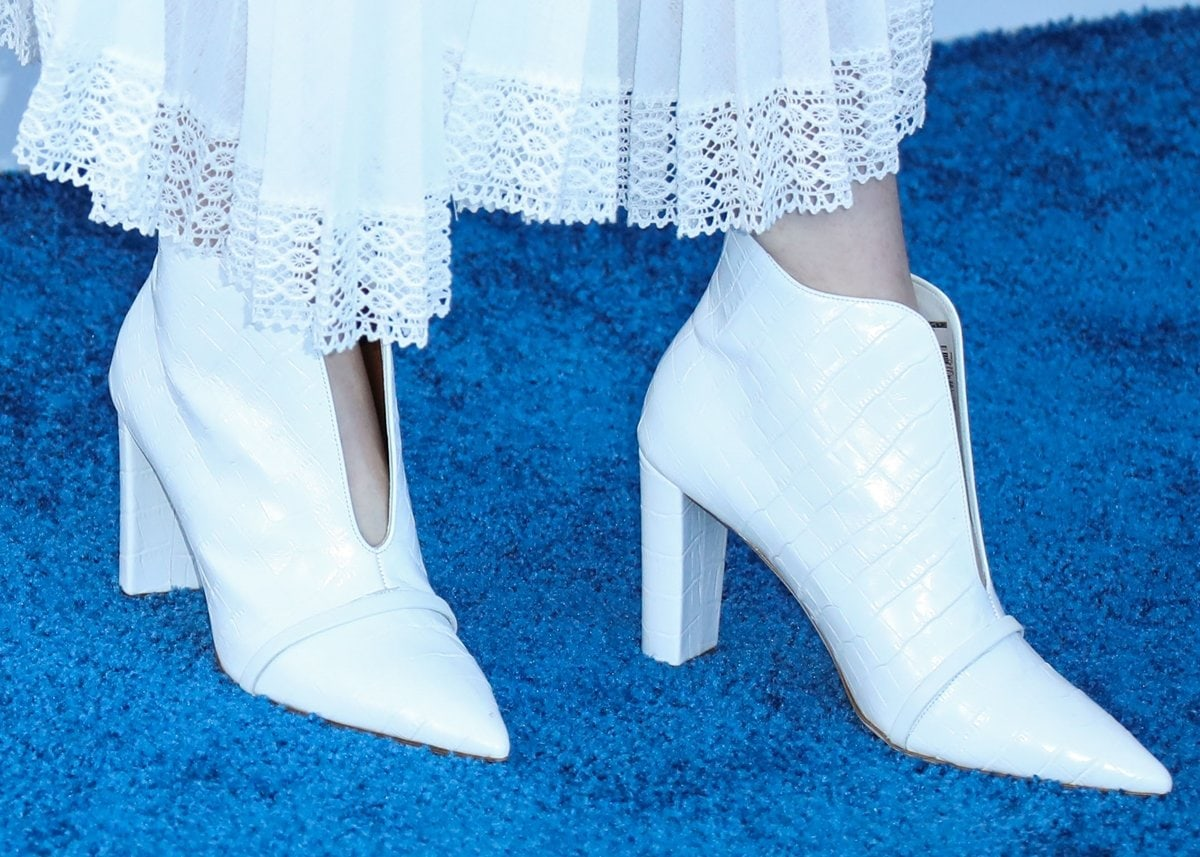 Hunter Schafer wears white Malone Souliers boots with a matching Loewe dress