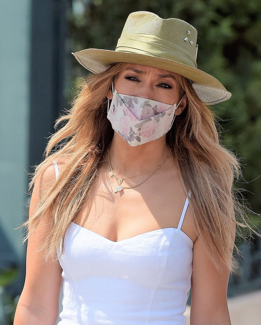 Jennifer Lopez wears a custom BEN necklace with a taupe flat-brim hat and a floral face mask