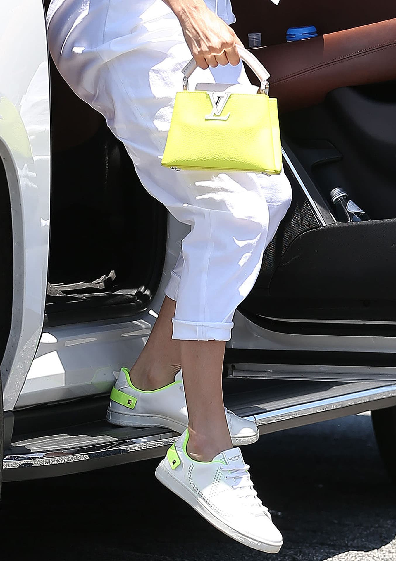 Jennifer Lopez coordinates her yellow Louis Vuitton Capucines Mini bag with her Valentino Backnet Vlogo sneakers