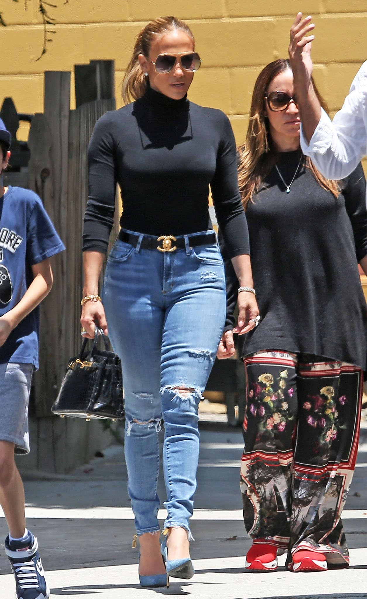 Jennifer Lopez flaunts her curves in a fitted black turtleneck top and form-fitting ripped jeans with a Chanel belt