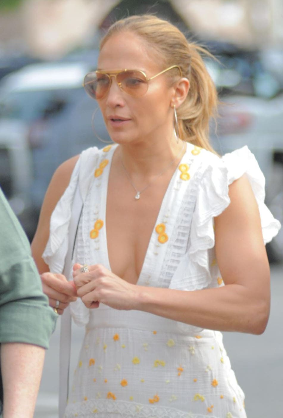 Jennifer Lopez displays her cleavage in her summery white frock styled with large hoop earrings and aviators