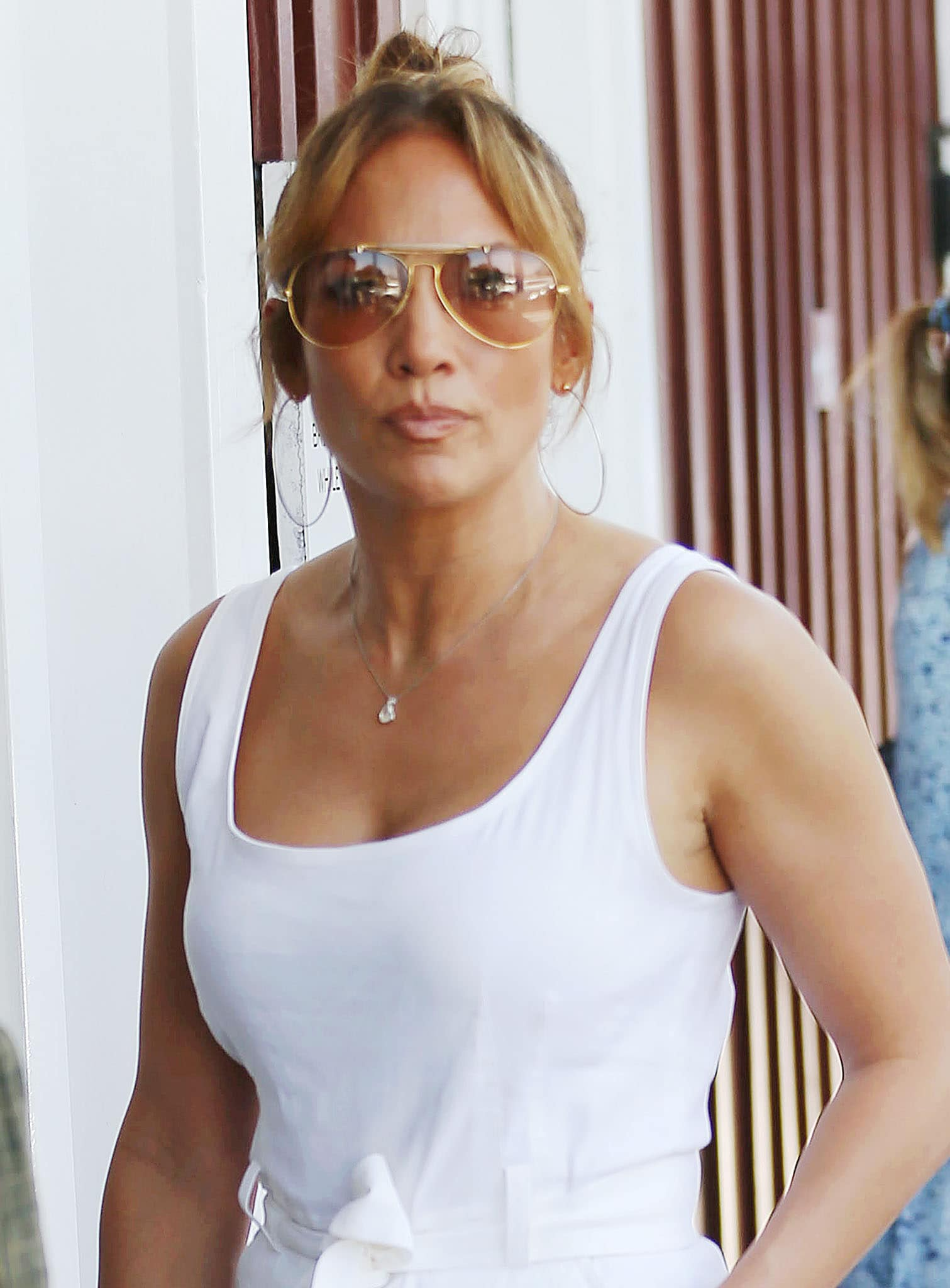 Jennifer Lopez styles her hair in a top knot and wears nude lipstick with Bausch & Lomb aviators