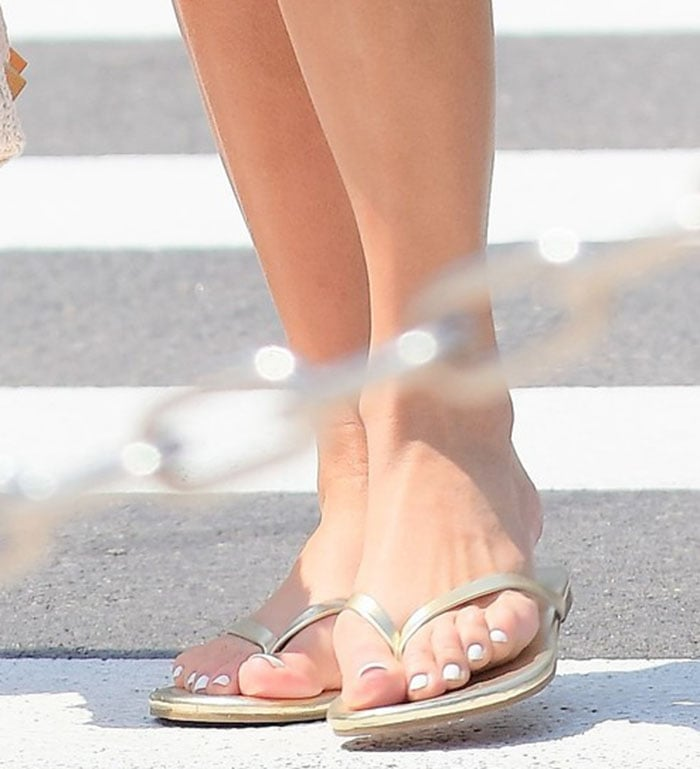 Jennifer Lopez completes her laid-back holiday look with metallic gold flip-flops