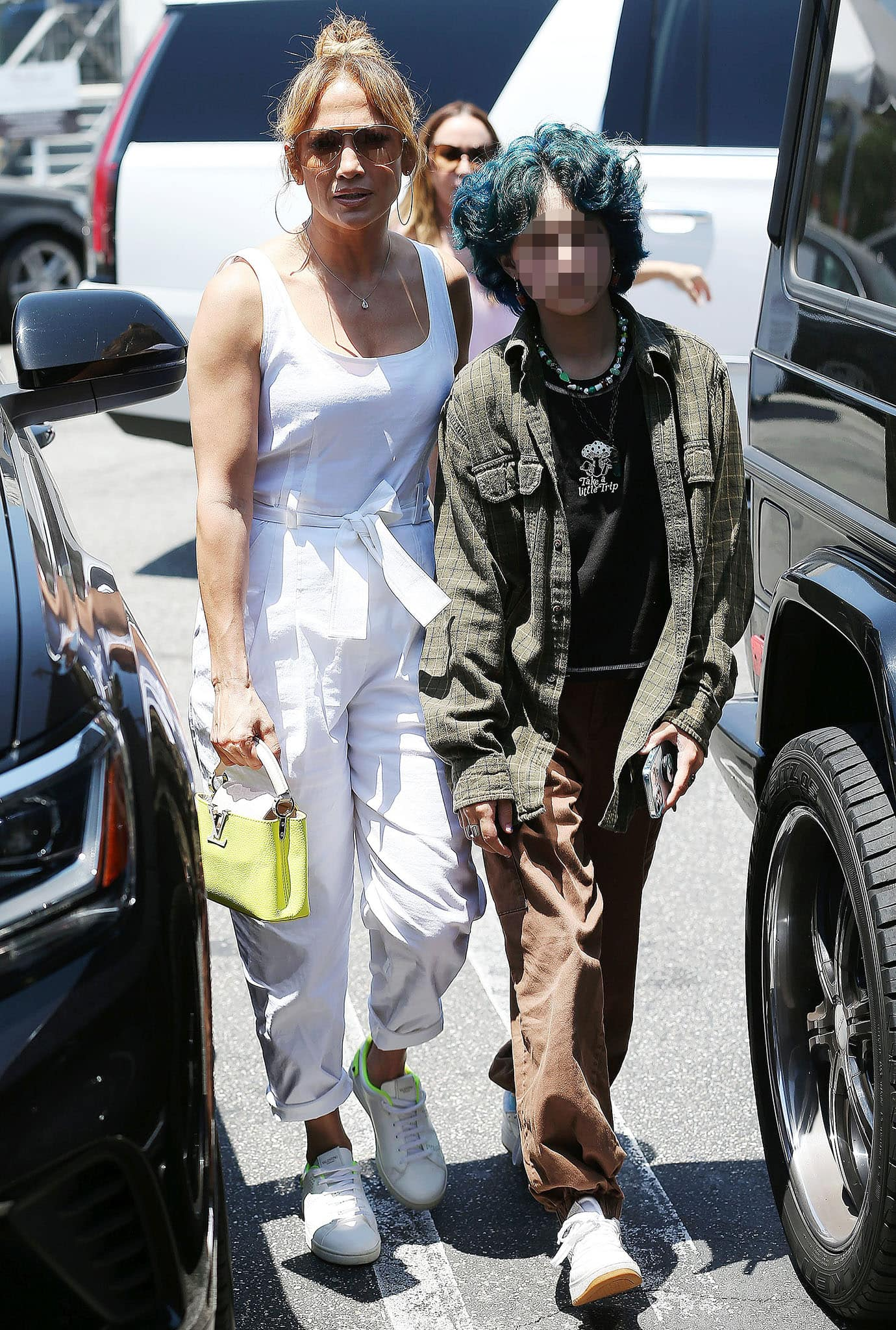 Jennifer Lopez's daughter, Emme, rocks curly green hair with oversized plaid shirt and baggy pants