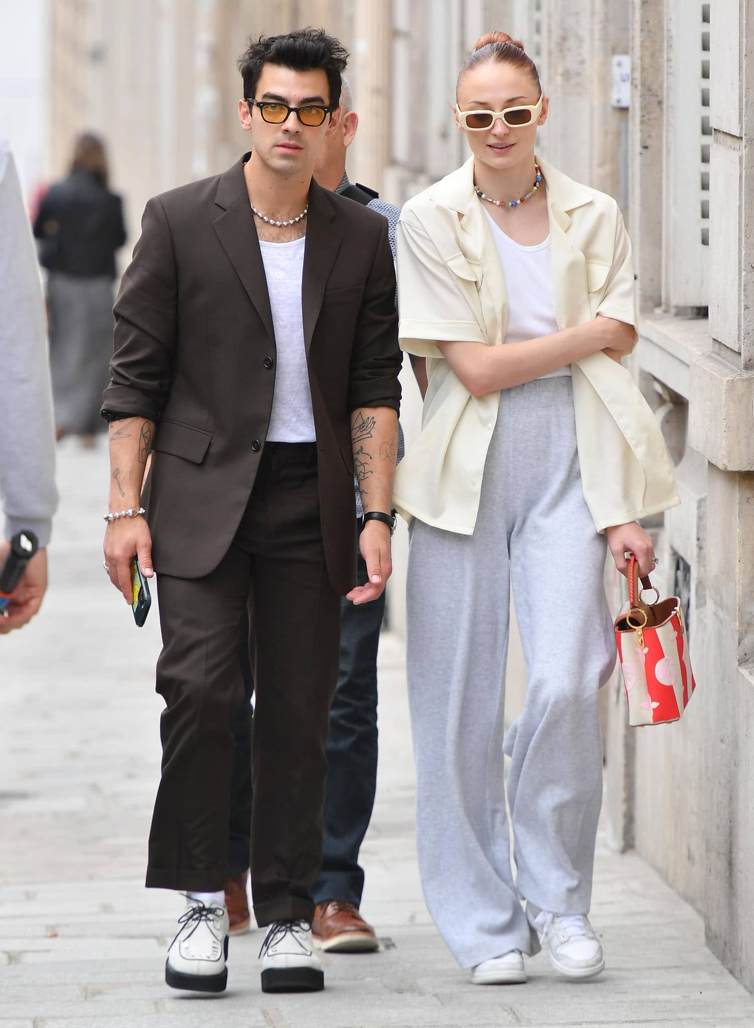 Joe Jonas looks handsome in his brown pantsuit with a white tee, brogues, and yellow-tinted sunglasses