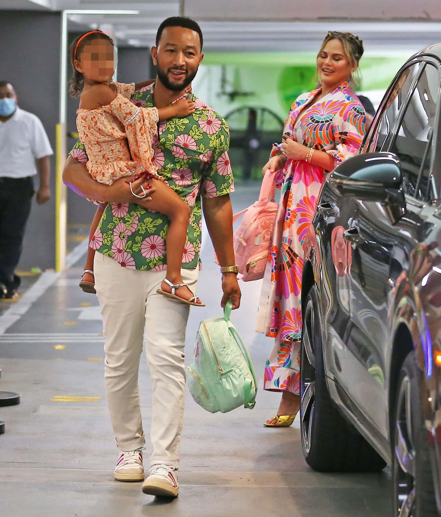 John Legend wears a green Hawaiian shirt as he carries daughter Luna