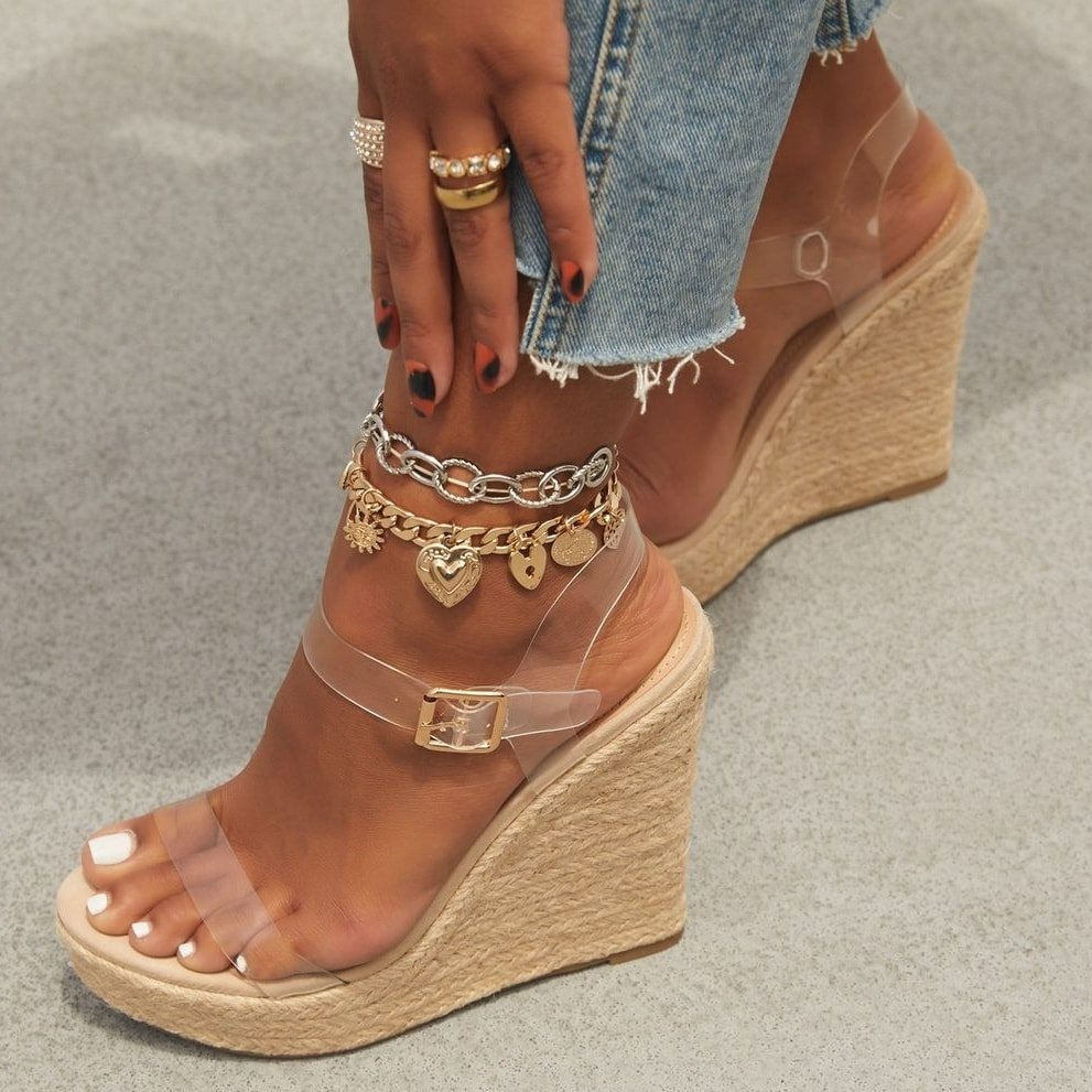 A beige espadrille wedge with transparent straps and a side buckle closure