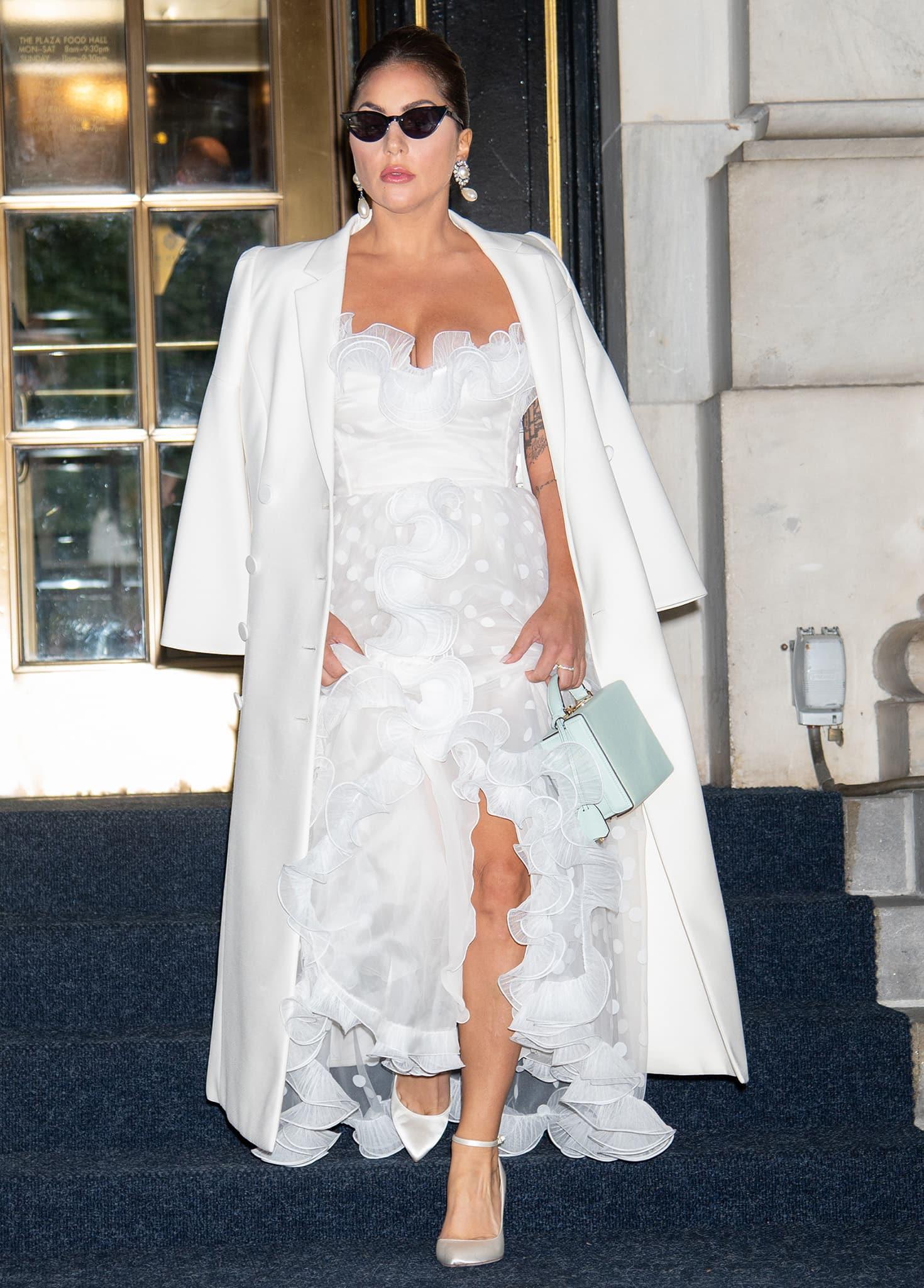 Lady Gaga pairs her Giambattista Valli white tulle ruffled dress with a Fendi wool-blend coat