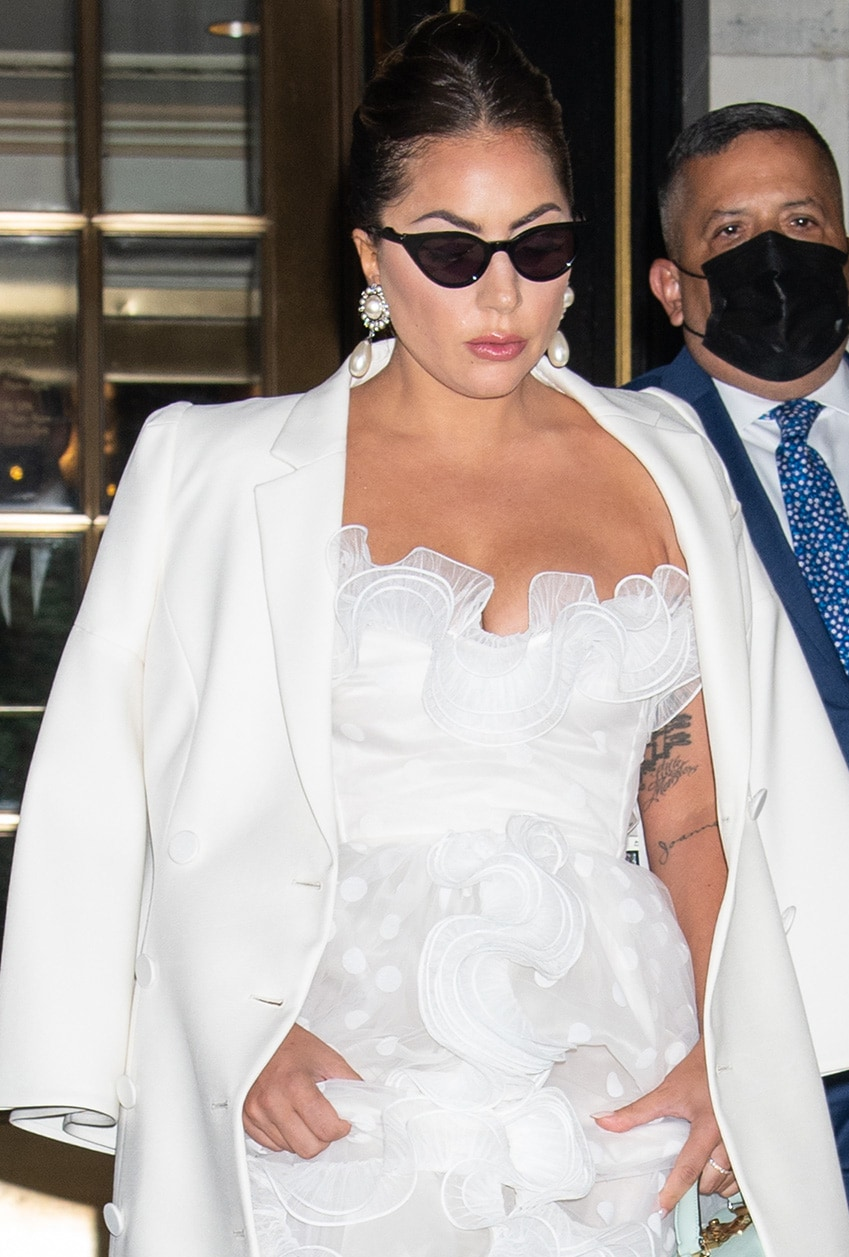 Lady Gaga accessorizes with Alessandra Rich earrings and wears a center-parted French twist with pink lip gloss