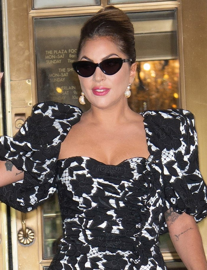 Lady Gaga wears a French twist bun and covers her eyes with retro cat-eye sunglasses