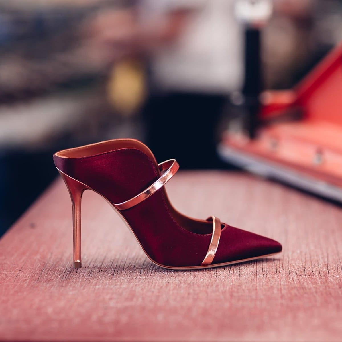 The iconic Maureen mules from London-based label Malone Souliers in lustrous wine-red satin with glossed rose gold leather panels