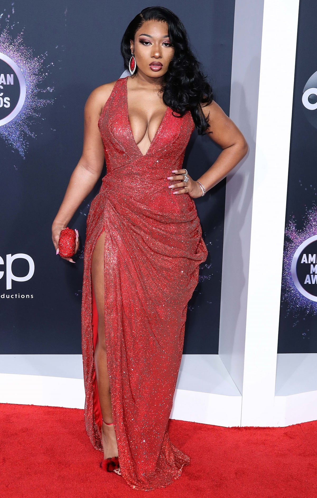Megan Thee Stallion flaunts her cleavage in a red glitter maxi dress by LA-based fashion designer Bryan Hearns