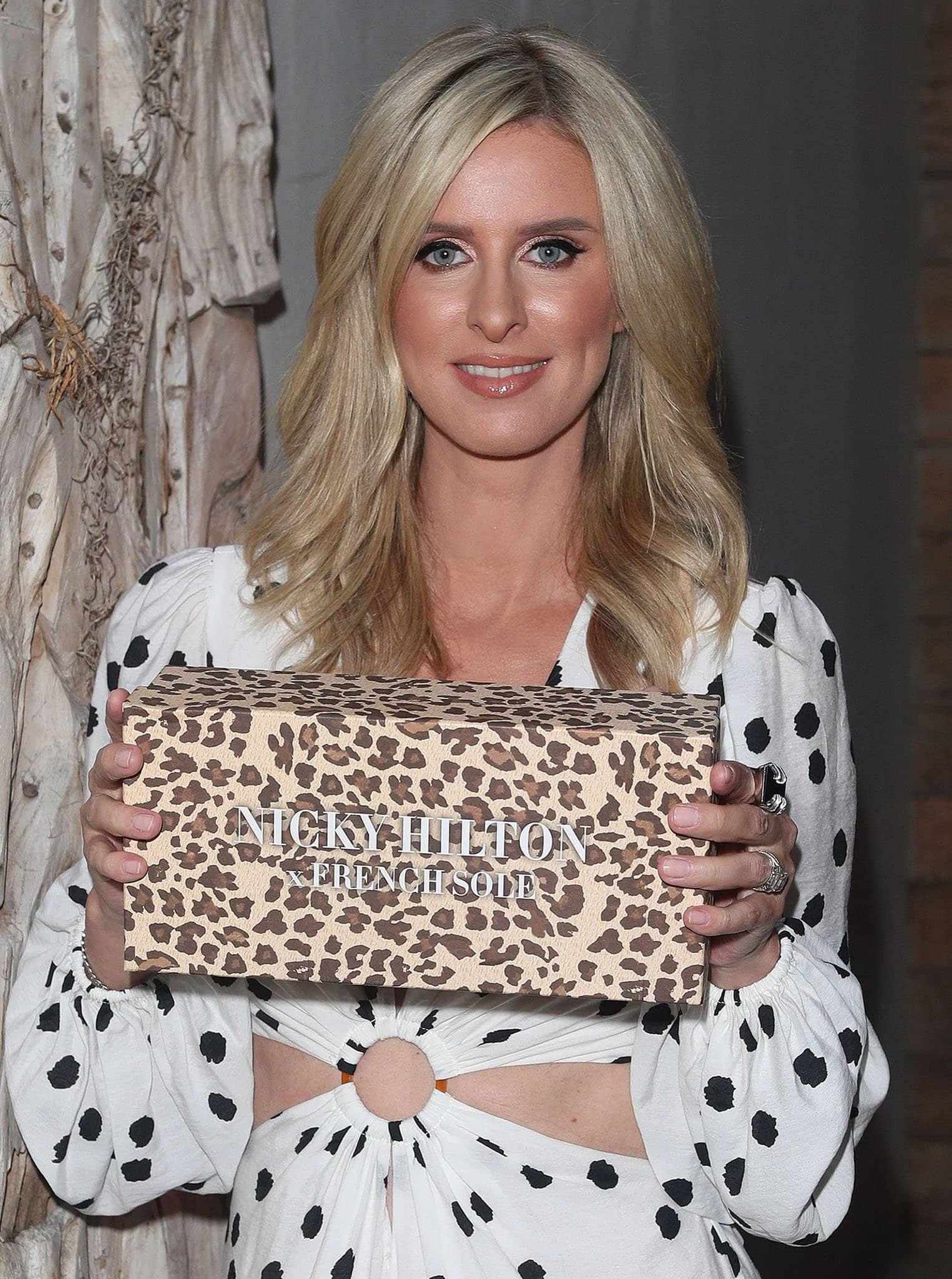 Nicky Hilton styles her hair in soft waves and wears peachy lipgloss with metallic pink eyeshadow and blush