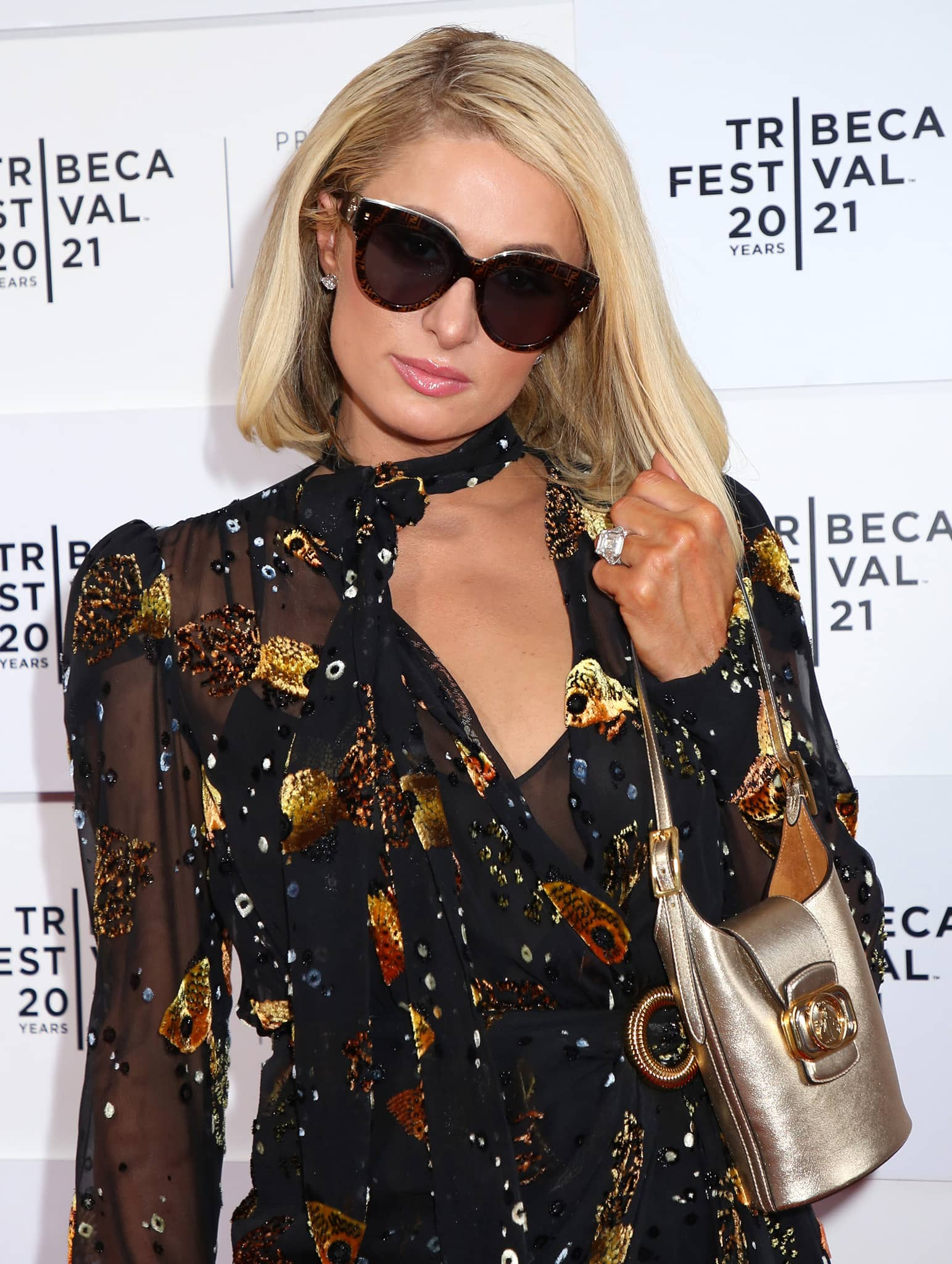 Paris Hilton shows off her engagement ring and accessorizes with Fendi sunglasses and Lanvin metallic gold bucket bag