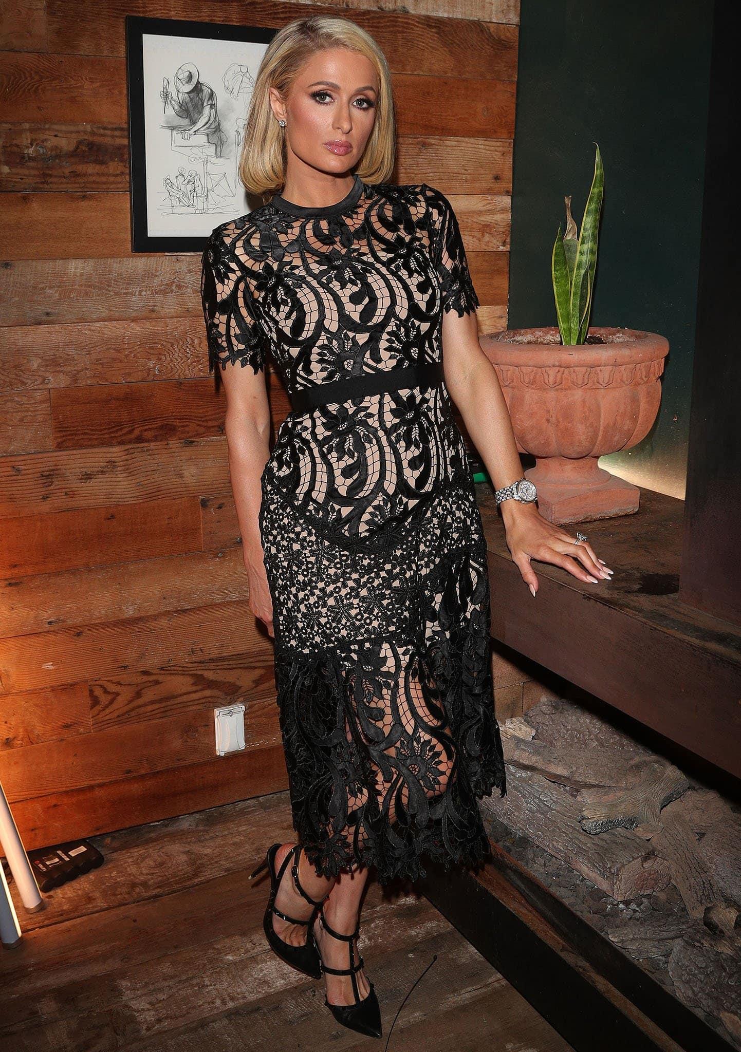 Paris Hilton looks sensational in a Self-Portrait black lace short-sleeved midi dress