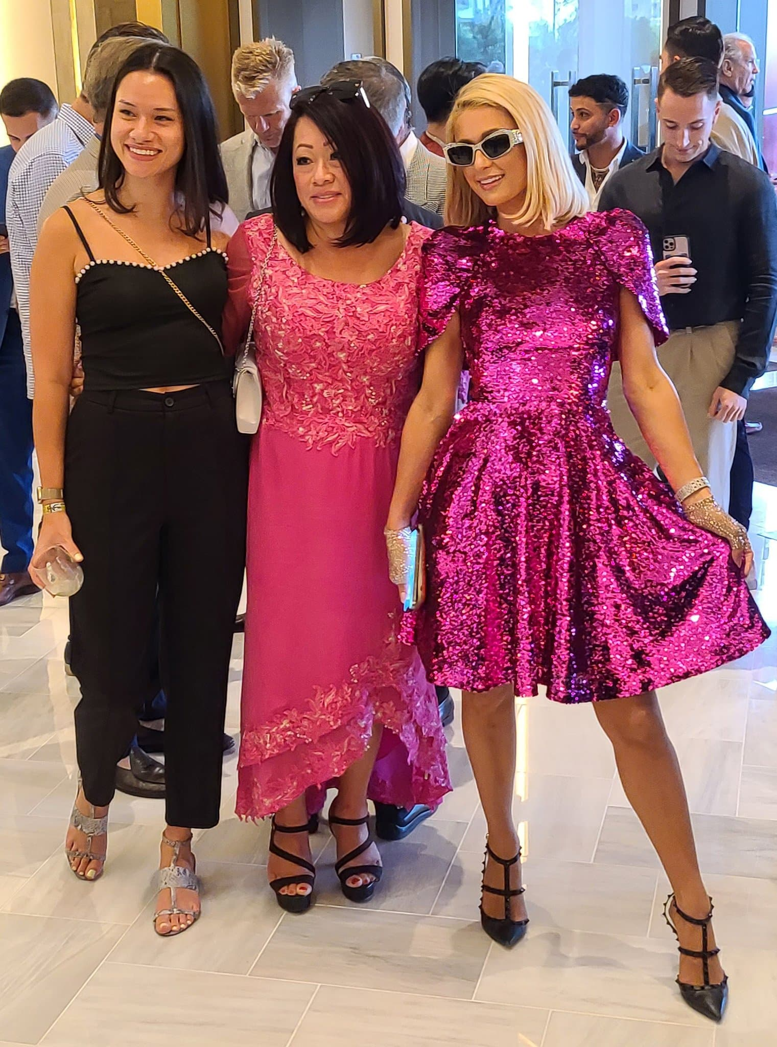 Paris Hilton poses with fans in a fuchsia pink sequined mini dress from Pamella Roland