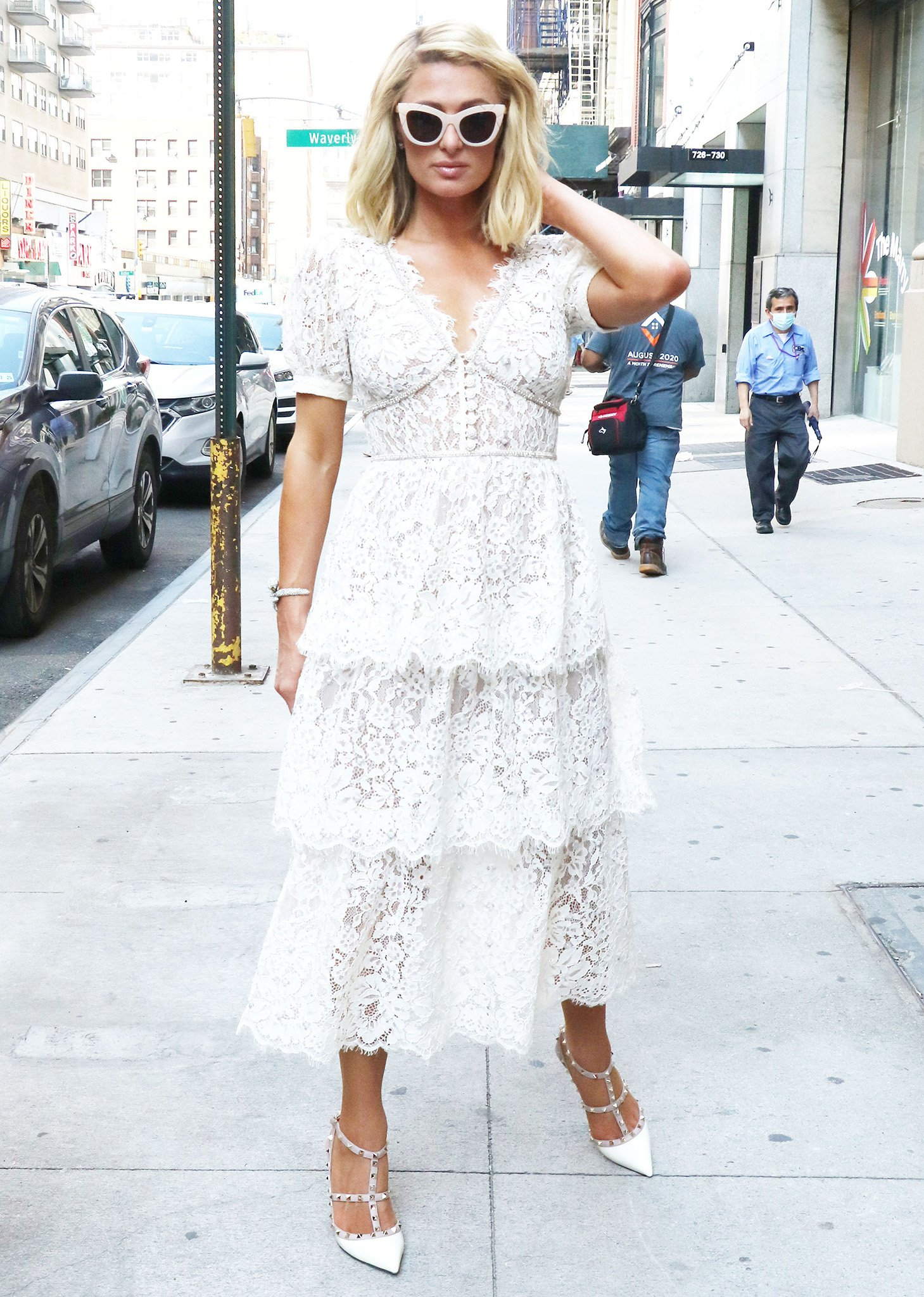 Paris Hilton looks ready for her wedding in a white lace tiered midi dress