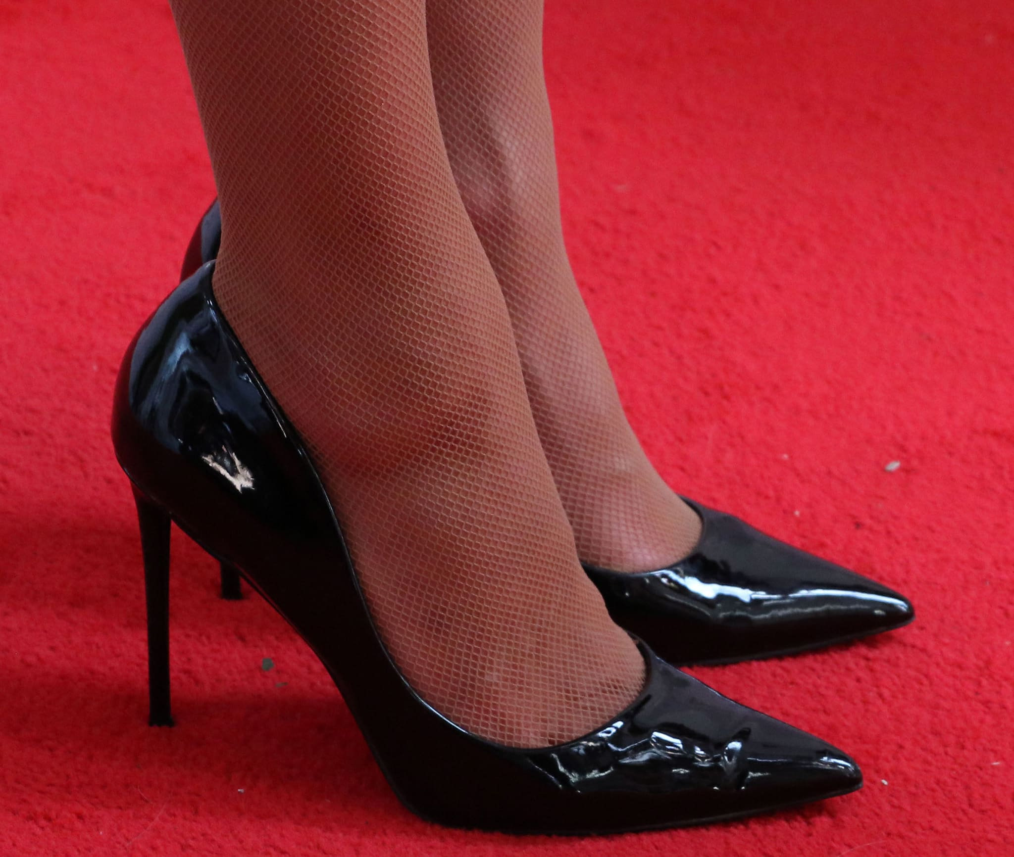 Paris Hilton shows off her feet in sheer fishnets and black patent leather pumps