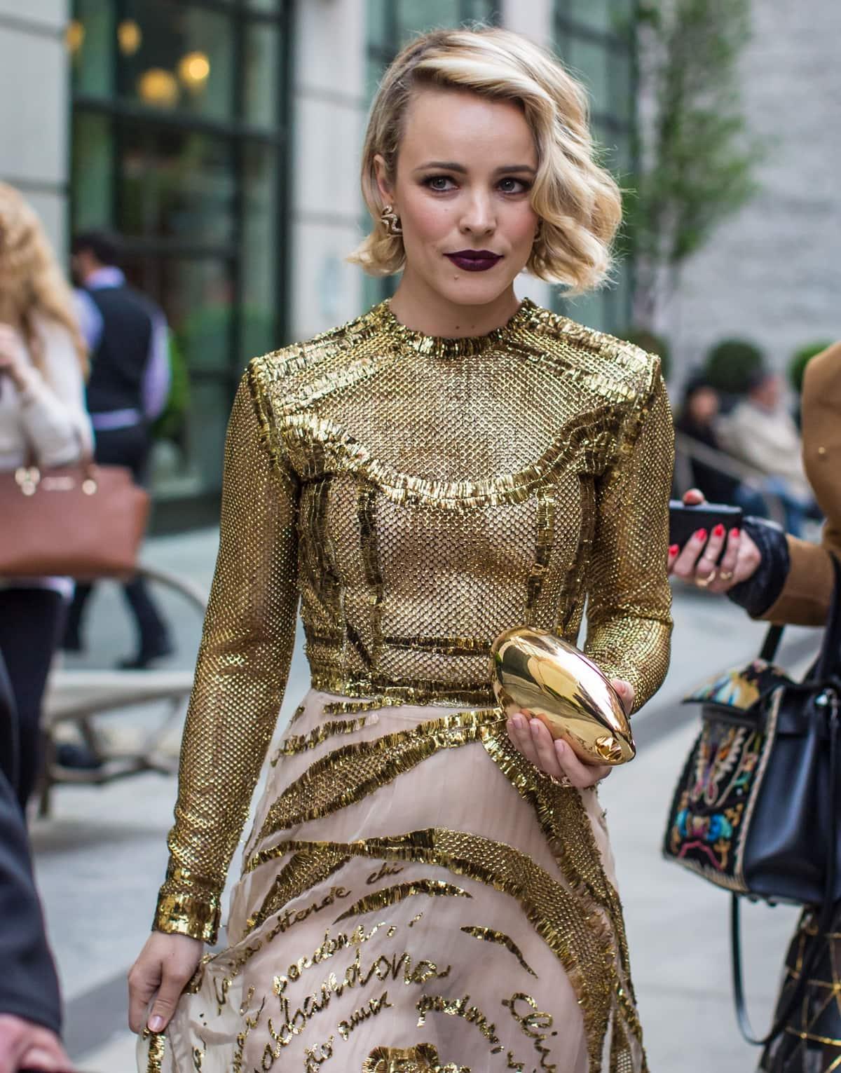Rachel McAdams wears a gold mesh Valentino dress and dark purple lip as she makes her way to the Met Gala