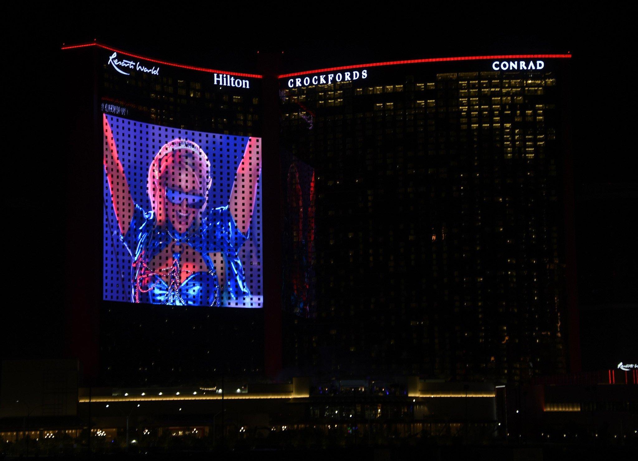 Paris Hilton is seen DJing on the big screen display during the grand opening of Hilton Resorts World Las Vegas on June 24, 2021