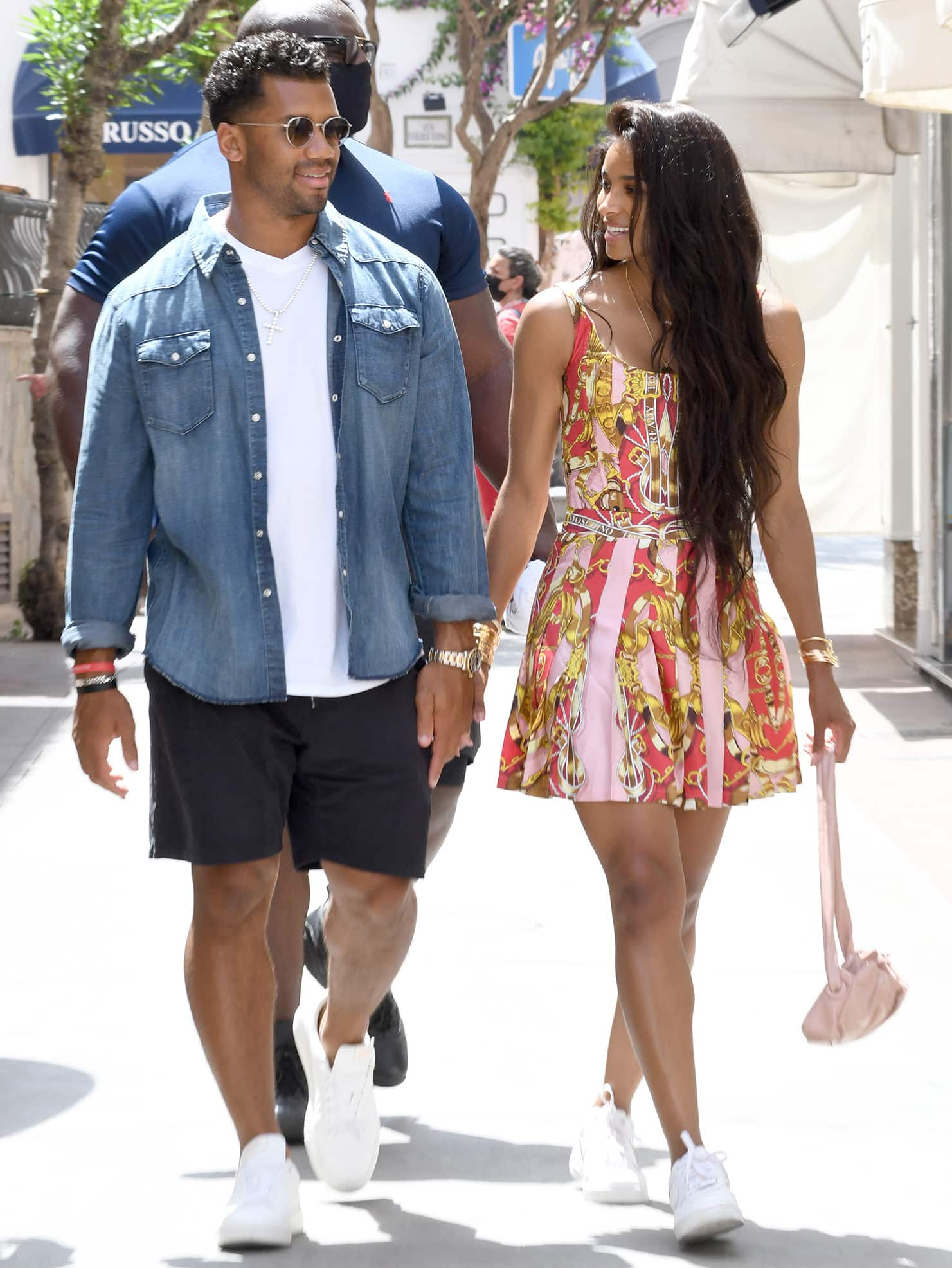 Russell Wilson is fresh in his white tee and shorts combo with a button-down denim shirt