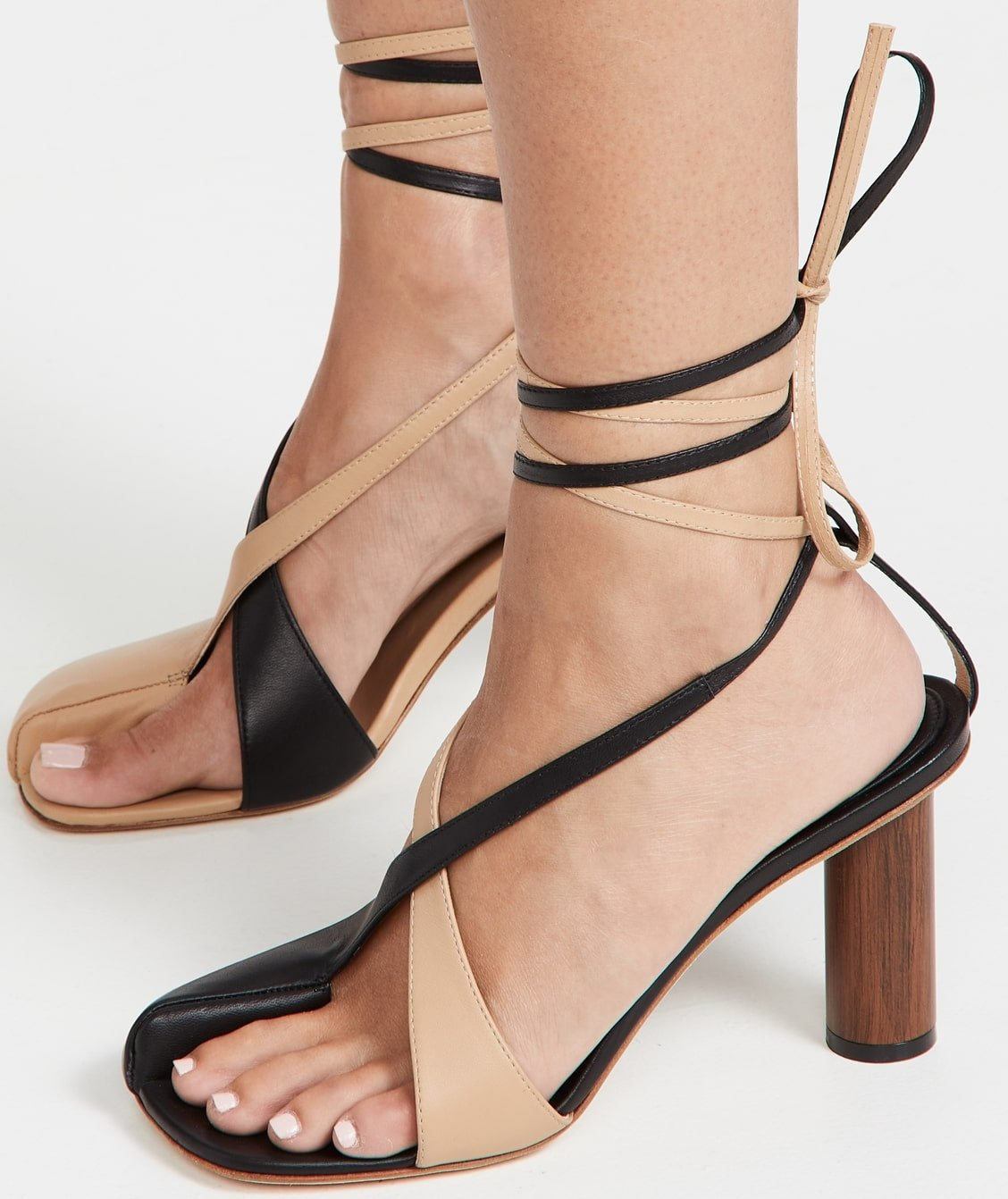 Beige and black asymmetrical open toe A.W.A.K.E MODE Geraldine wood heel sandals with wraparound ankle tie closure