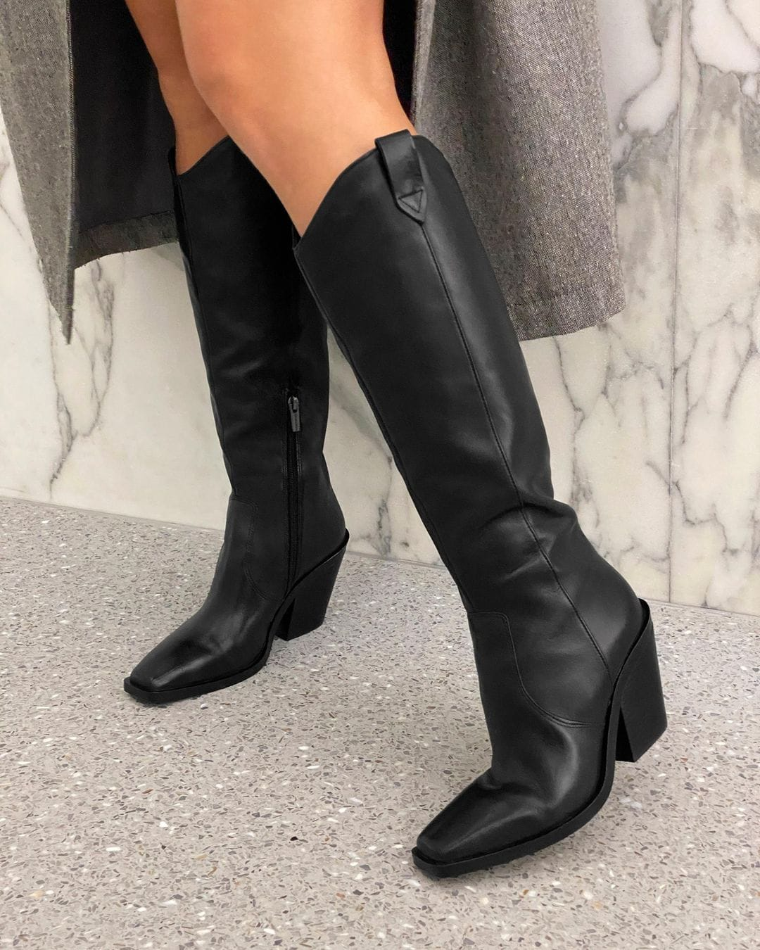 This black knee-high boot offers a subtle Western note with its curved topline, while a sleek squared-off toe and slanted, stacked heel gives it true city appeal