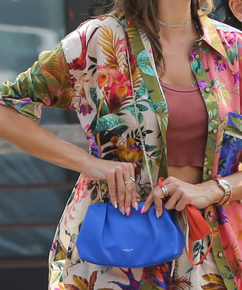 Alessandra Ambrosio adds bright color to her look with an electric blue DeMellier Mini Florence leather pouch clutch
