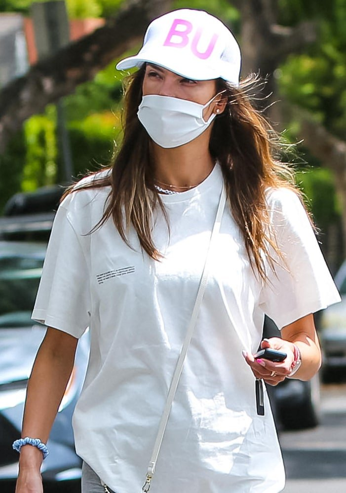 Alessandra Ambrosio keeps a low profile with a trucker cap from Fancy Lids and a white face mask