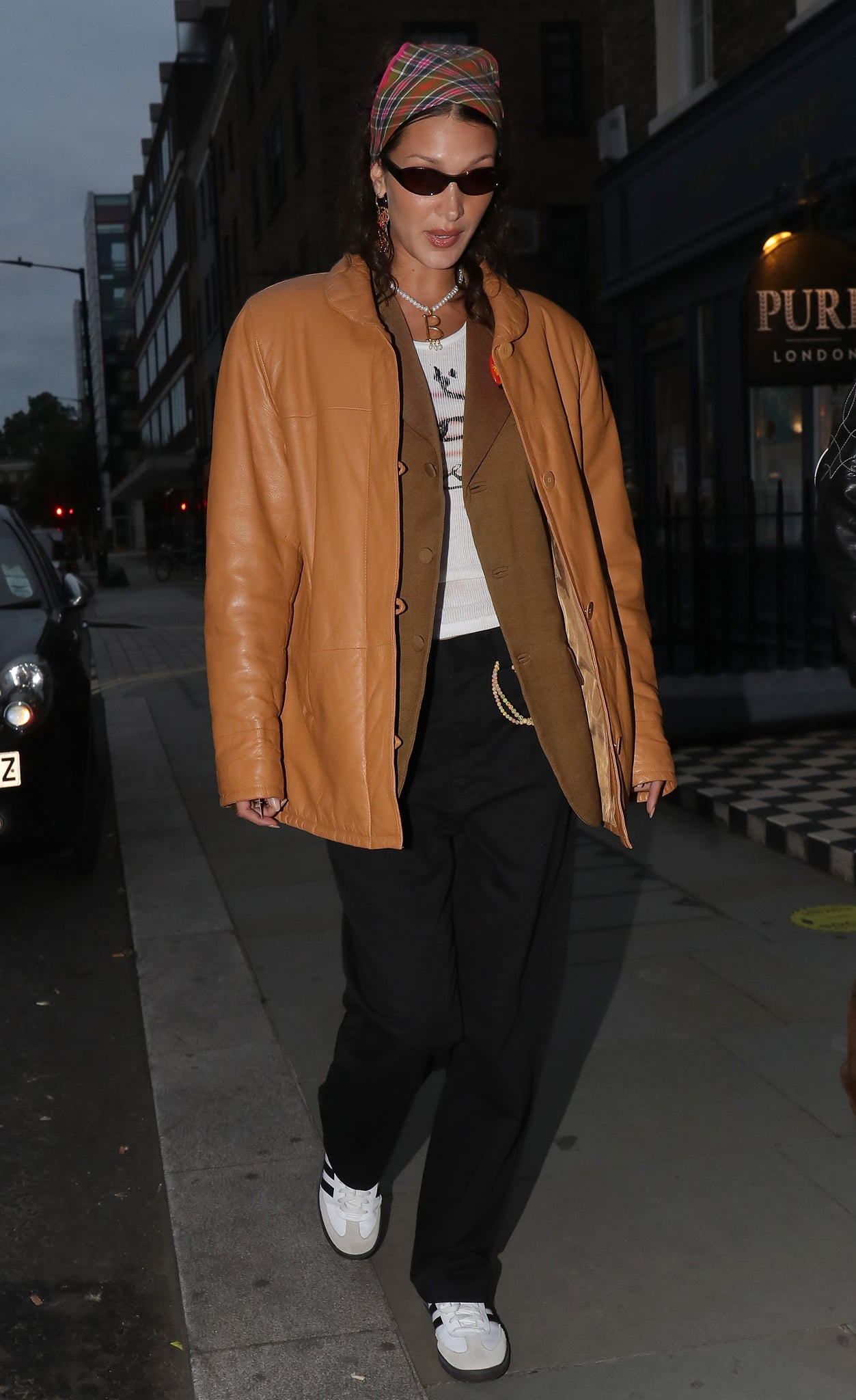 Bella Hadid bundles up in a mustard leather jacket and a brown blazer layered over a white tee and black pants