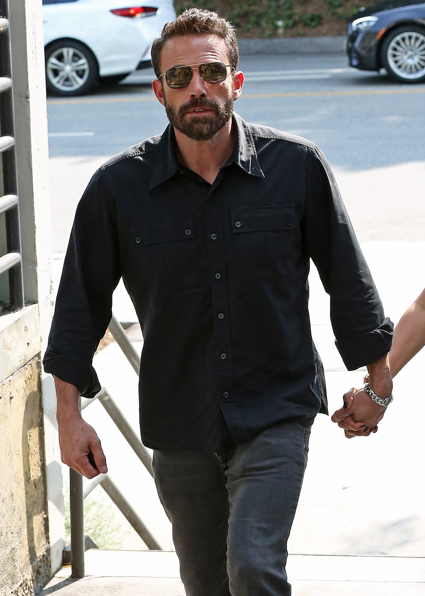 Ben Affleck looks handsome in his black shirt, gray pants, and aviator sunglasses