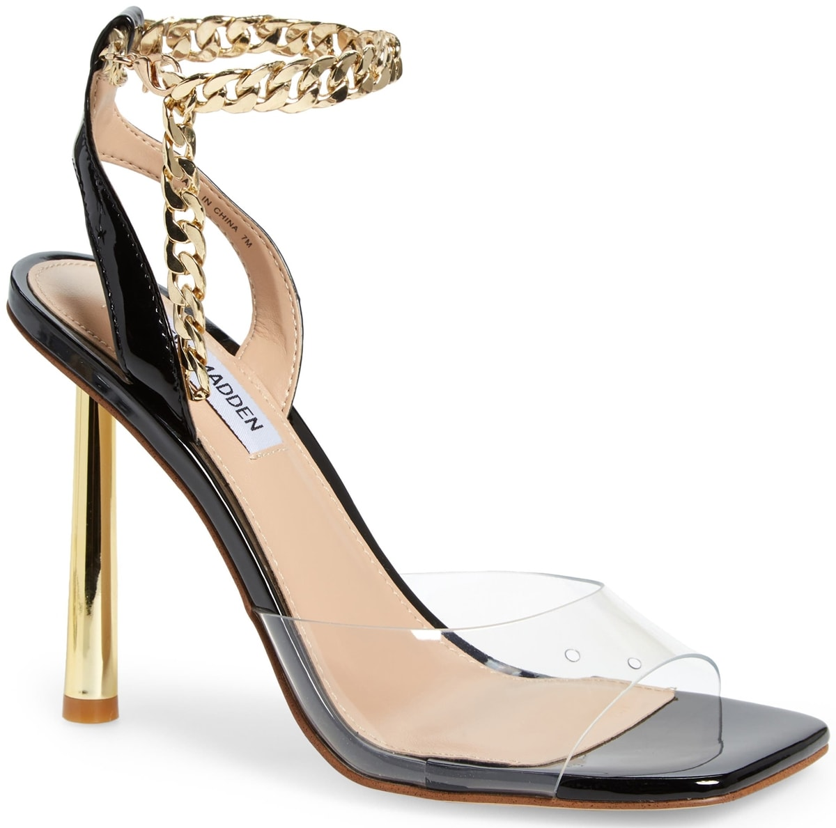 A chunky chain wraps around the ankle of a stunning black/clear sandal from Steve Madden set on a towering golden heel
