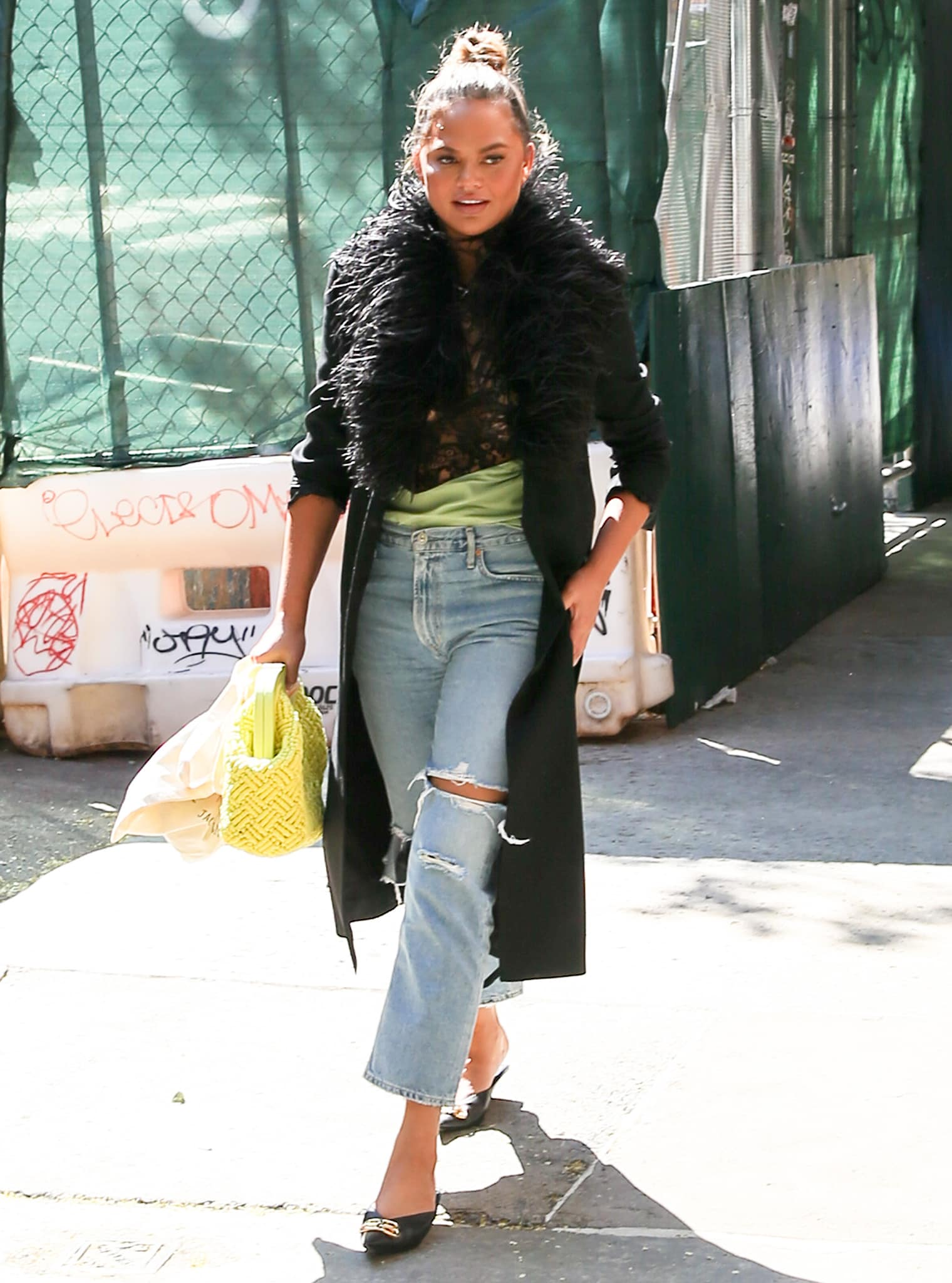 Chrissy Teigen's Saint Laurent feathered wool coat adds glam factor to her casual outfit