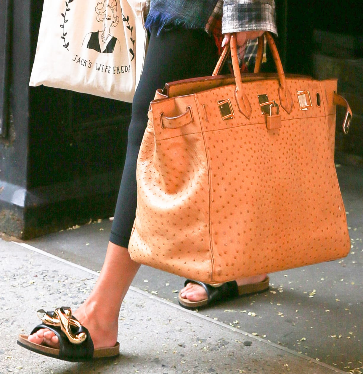 Chrissy Teigen finishes off her laidback outfit with Hermes Birkin bag and JW Anderson Chain slides