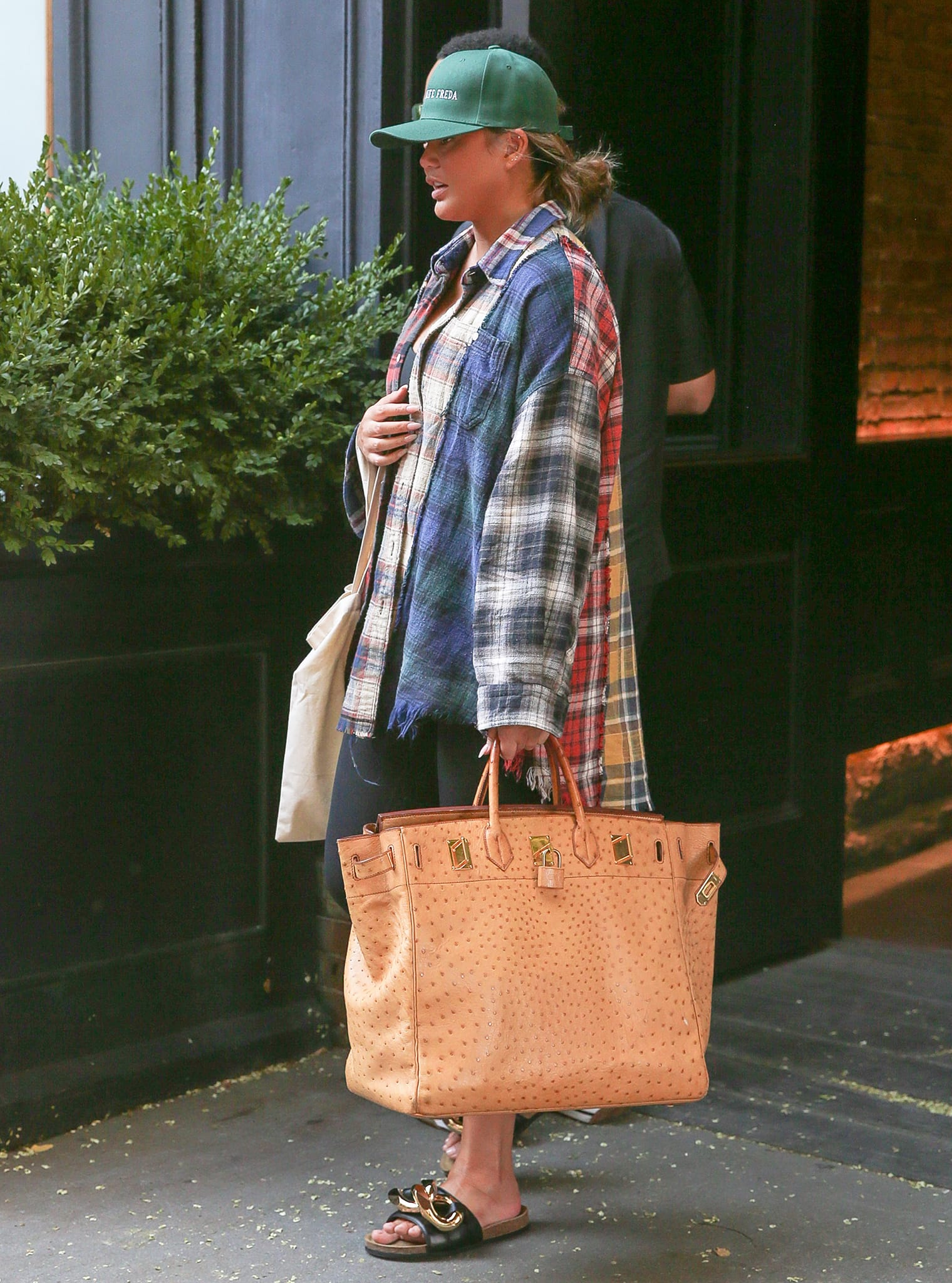 Chrissy Teigen leaving her apartment building in patchwork flannel shirt and leggings in SoHo, NYC on July 30, 2021