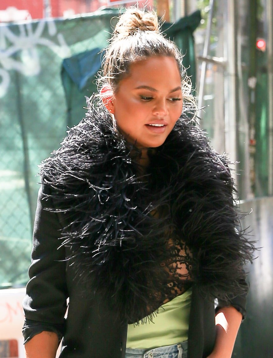 Chrissy Teigen wears a top knot with dewy neutral makeup that highlights her eyes