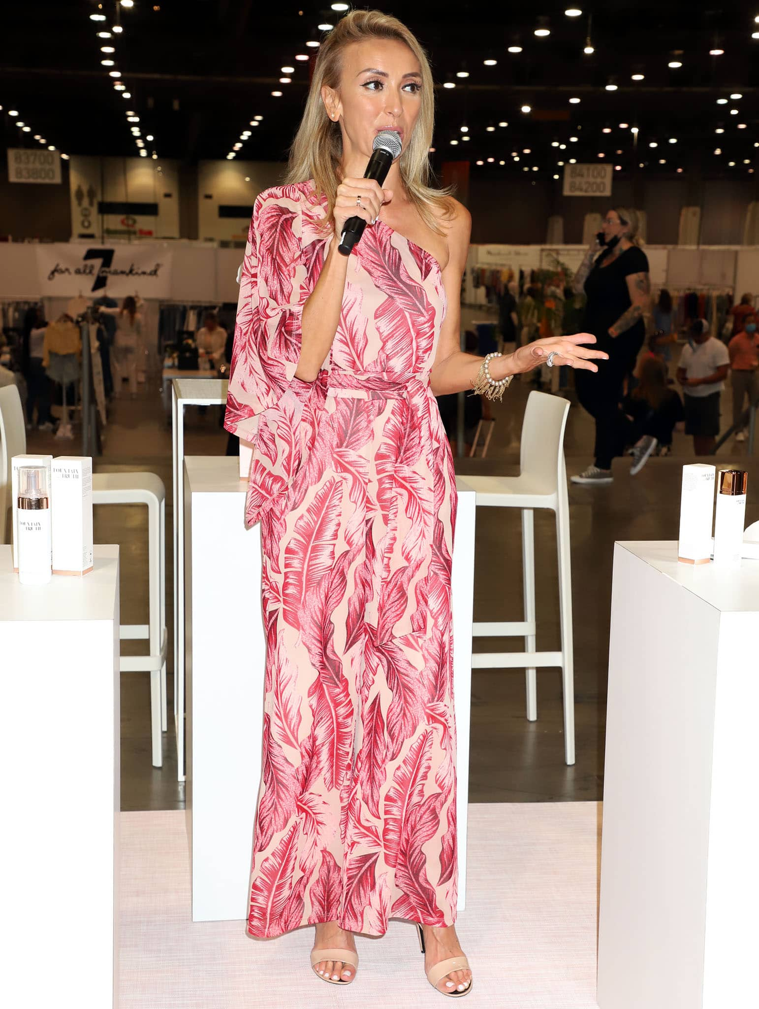 Giuliana Rancic's jumpsuit features pink banana leaf prints and a high-low long sleeve