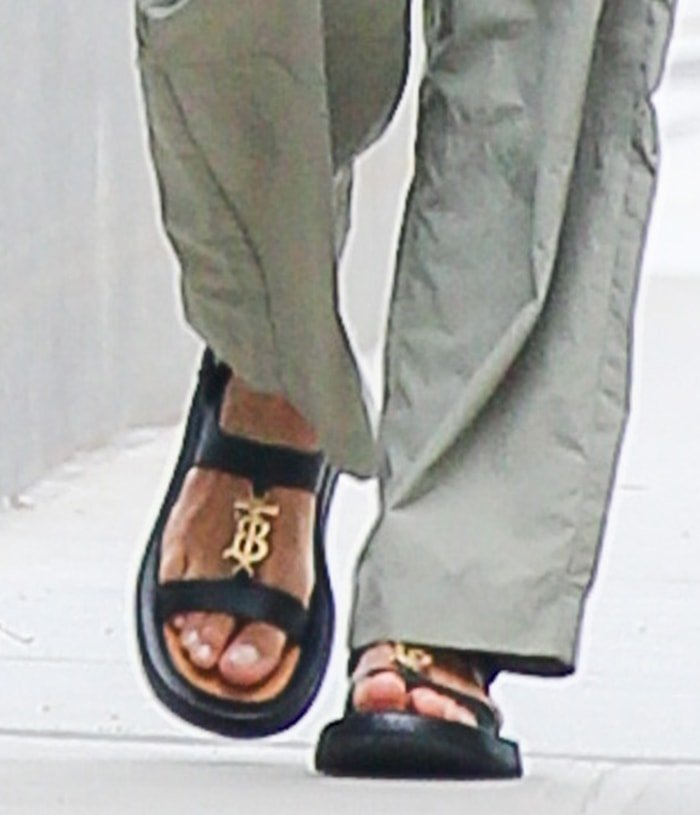 Irina Shayk completes her chic and sexy casual outfit by showing off her feet in Burberry logo-plaque sandals