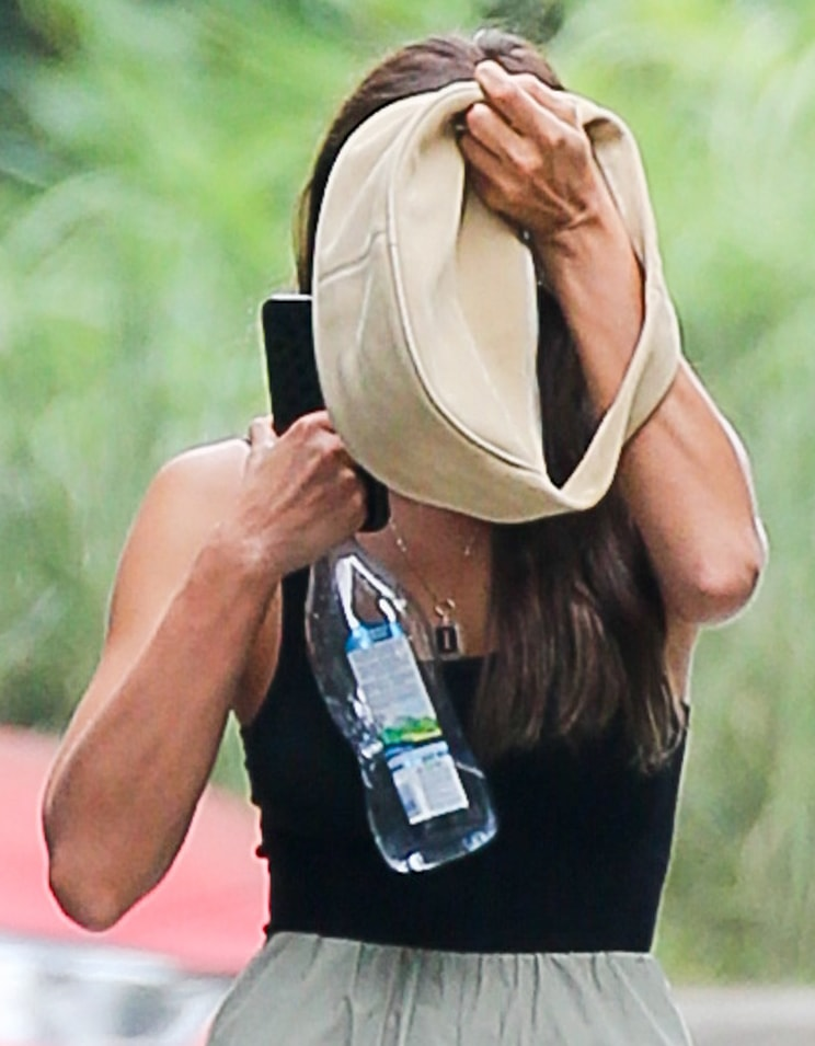 Irina Shayk hides her face from the paparazzi behind her beige suede bag